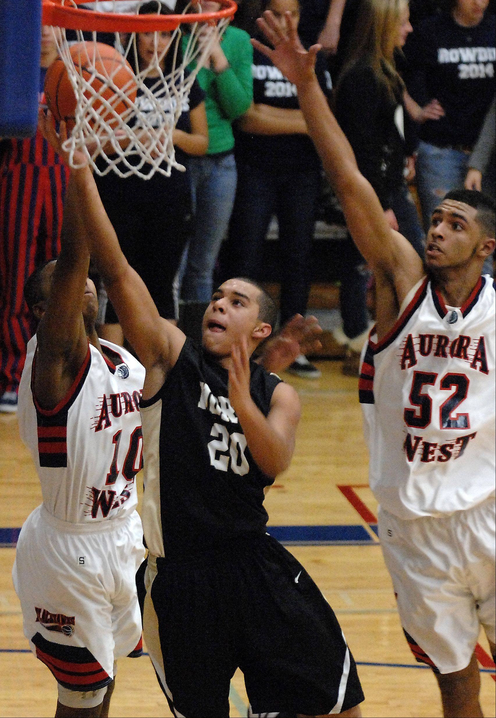 Glenbard North's Kendall Holbert scores between a pair of West Aurora defenders.
