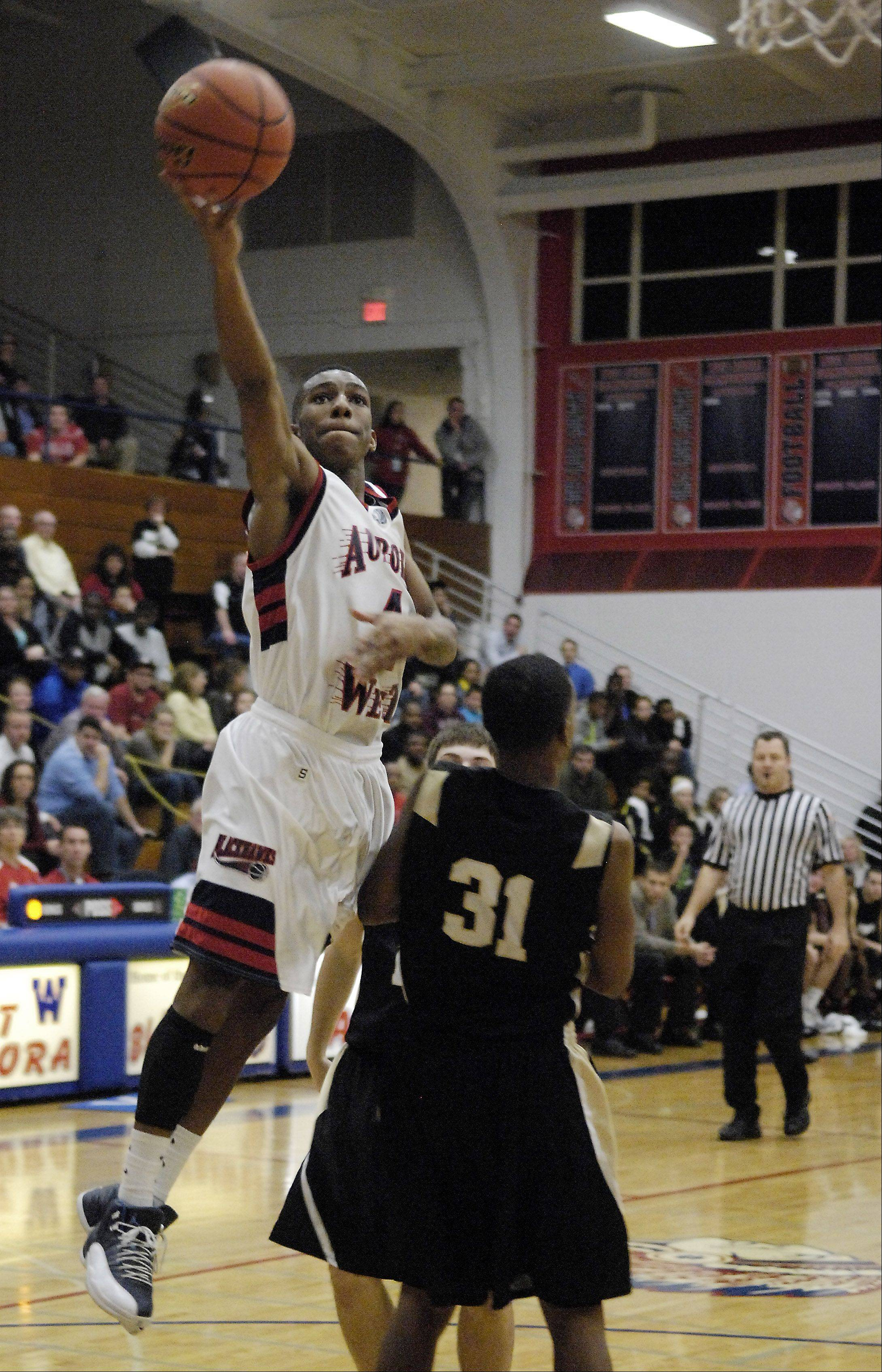West Aurora's Jayquan Lee glides in for a layup over Glenbard North's Chavares Flanigan .