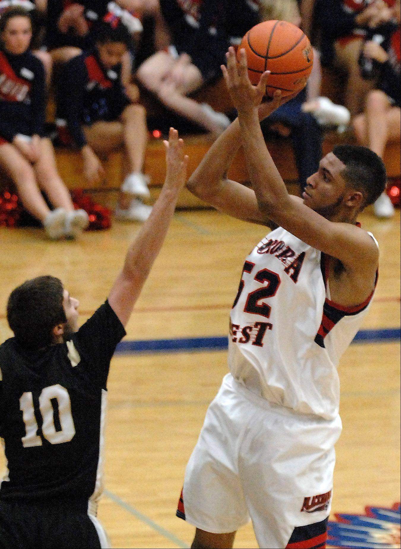 West Aurora's Joshua McAuley shoots and scores over Glenbard North's Paxquale Fiduccia.