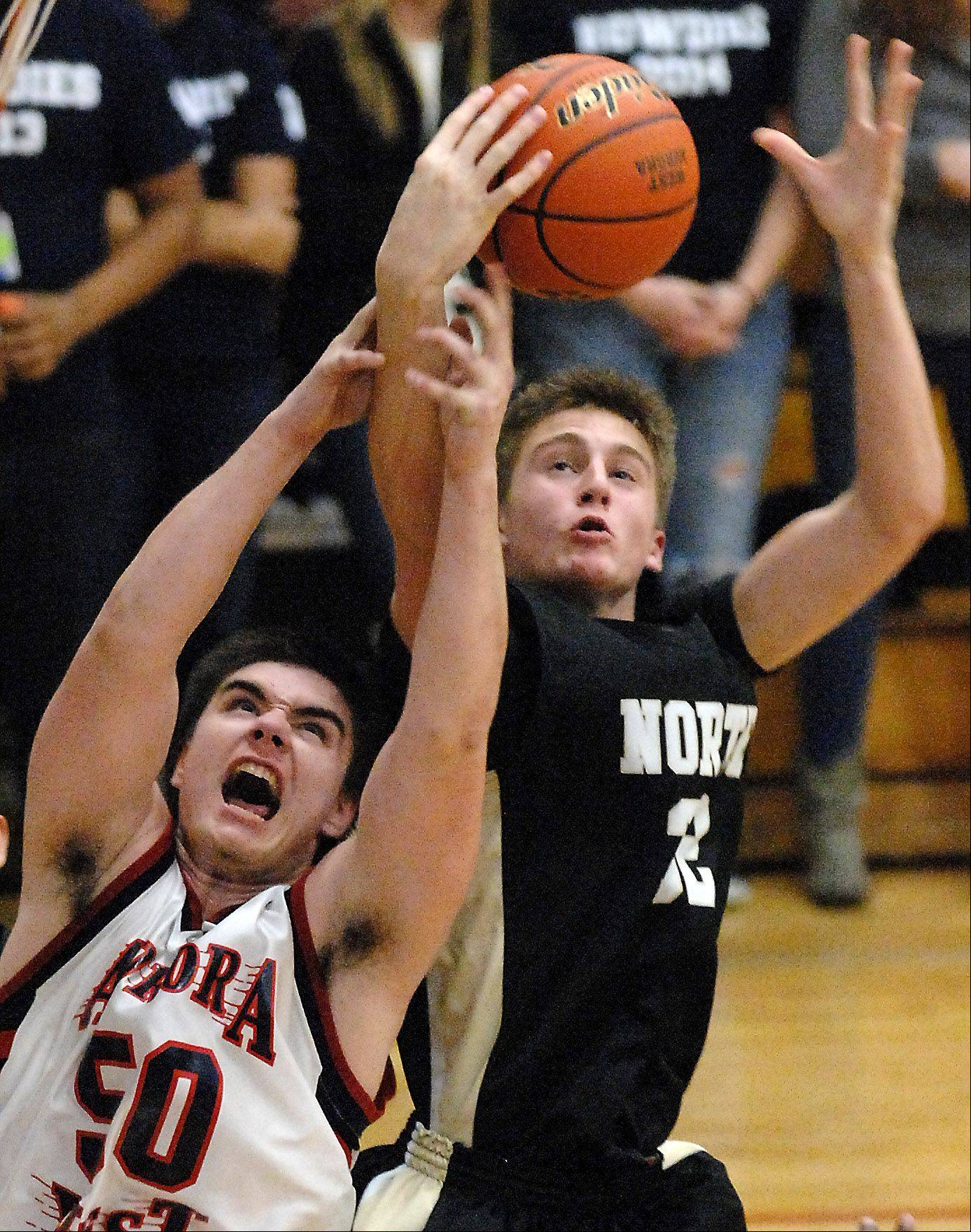 West Aurora's Chandler Thomas battles for a rebound with Glenbard North's Brett Gasiorowski.
