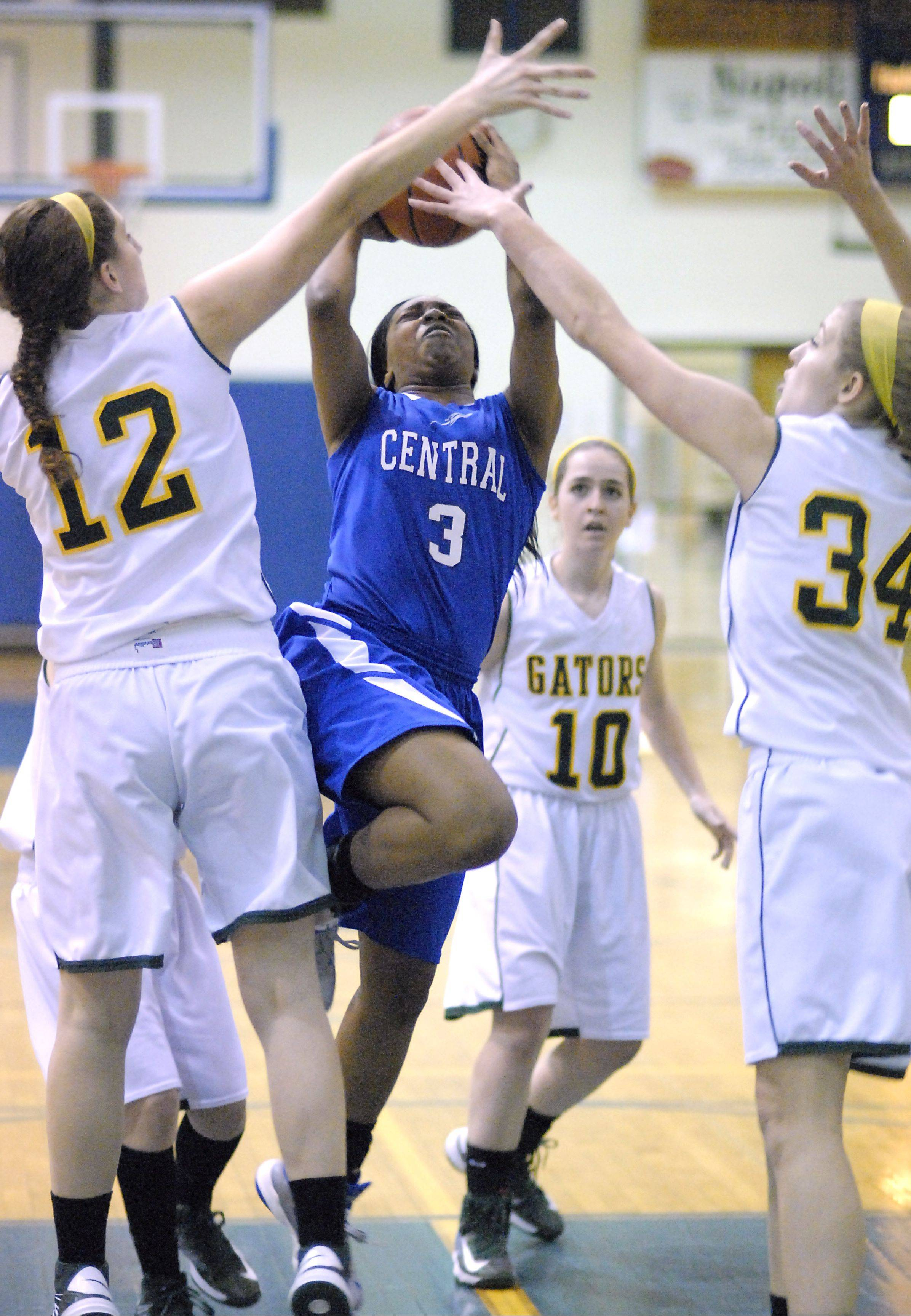 Burlington Central's Erica Haynes makes it past the defense of Crystal Lake South's Carly Nolan and Sara Mickow to score a basket during the Northern Illinois Holiday Classic at Woodstock Saturday.