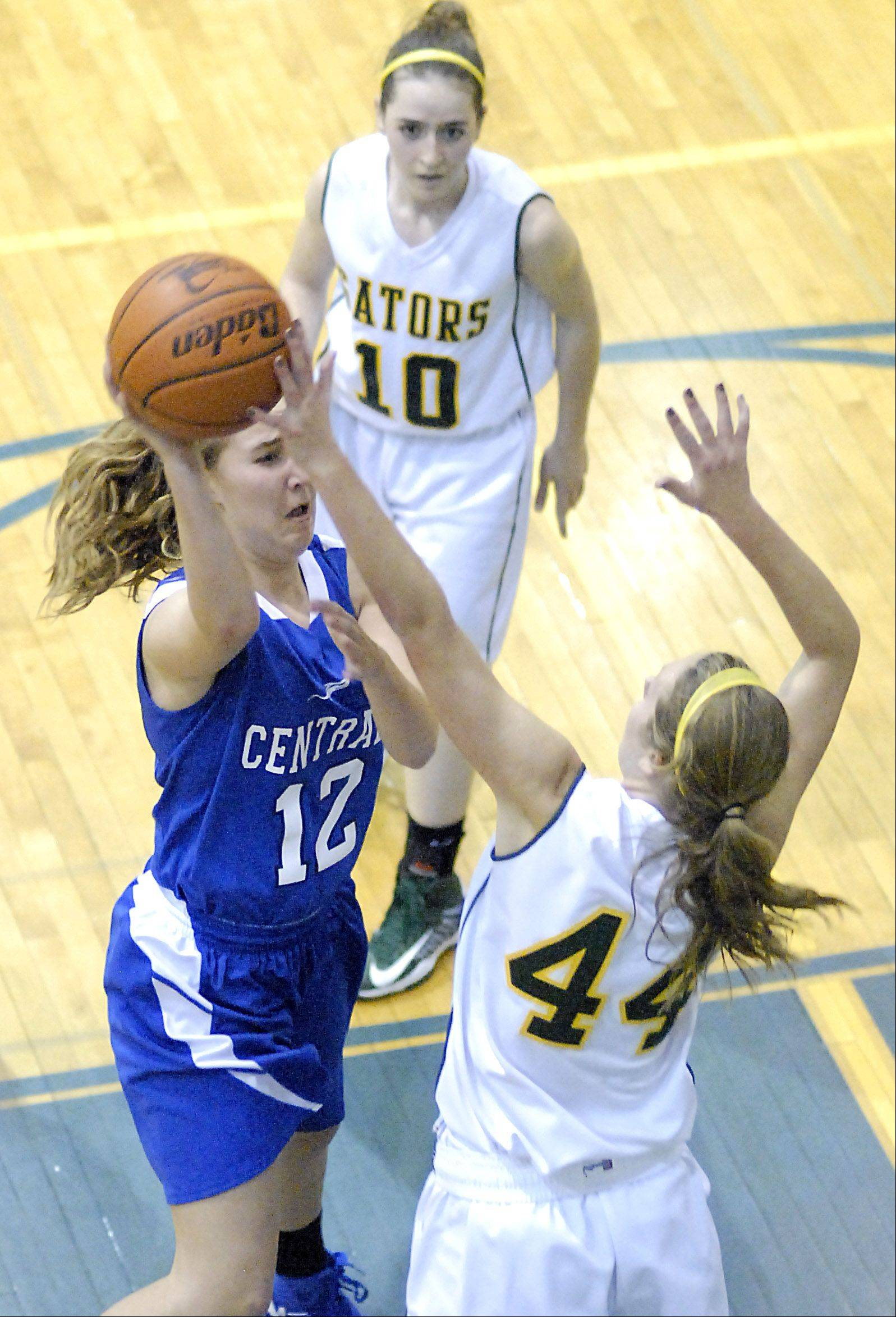Burlington Central's Shelby Holt attempts to shoot past a block by Crystal Lake South's Lauren Del Vecchio Saturday in Woodstock.