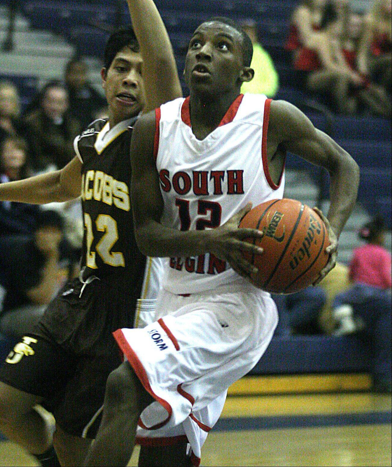 Jacobs' Patrick Nerja, left, tries to catch South Elgin's Devonte Cager near the hoop at South Elgin on Tuesday night.