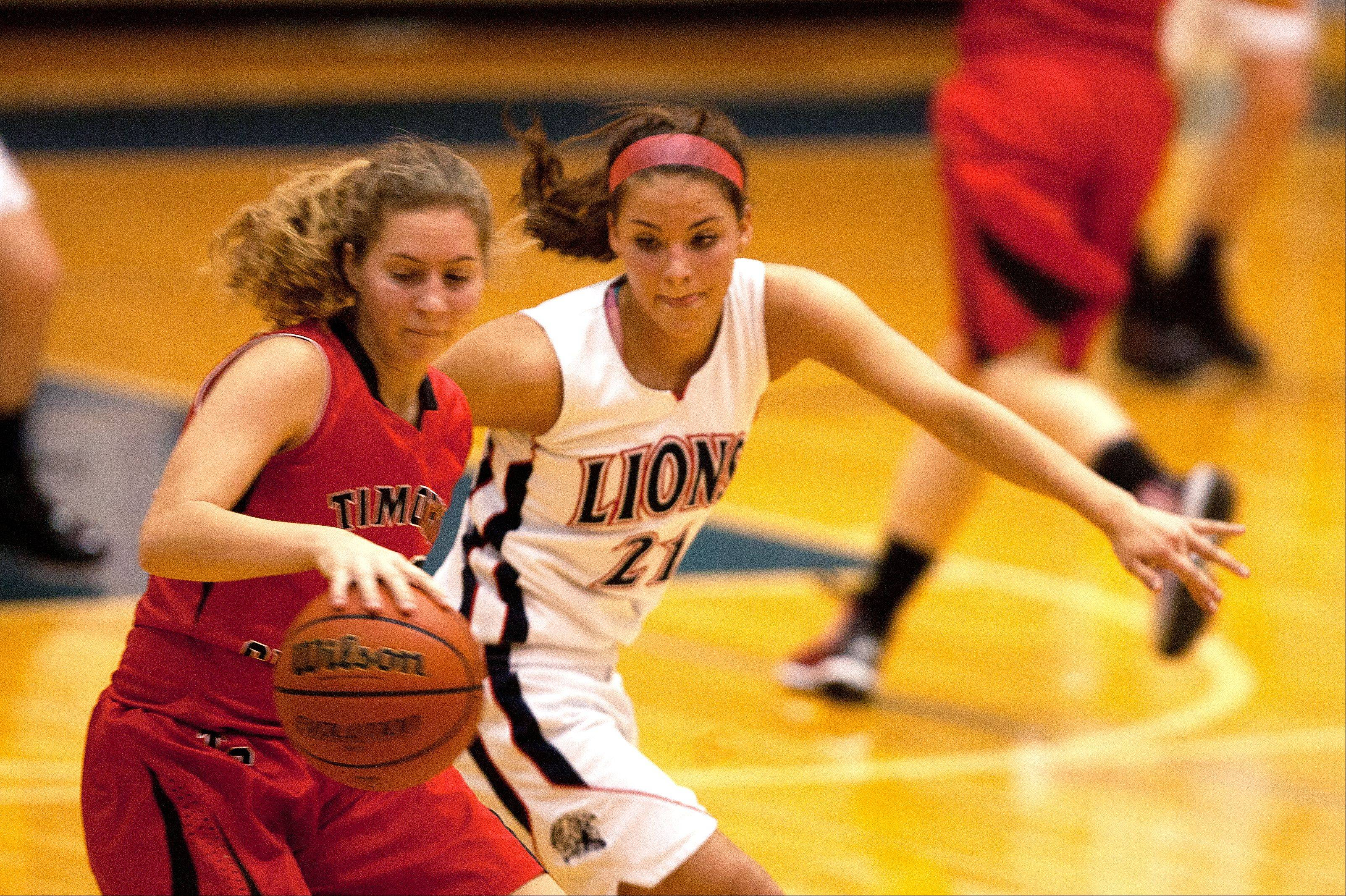 Timothy Christian's Sara Hodges, left, moves past Lisle's Kelly Urban, right, during girls basketball action at Lisle.