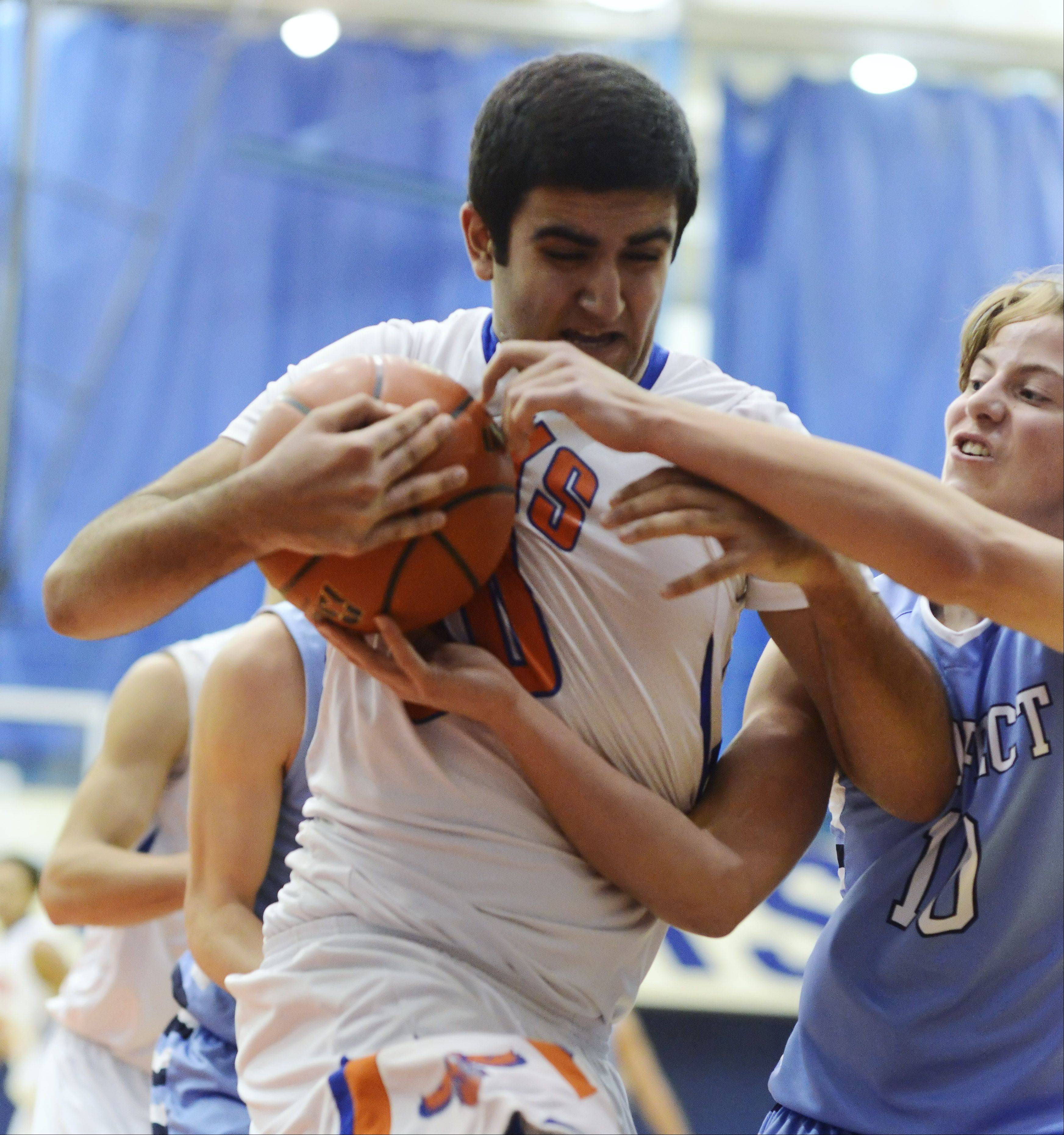 Hoffman Estates' Joe Biko tries to keep the ball from the grasp of Prospect's Nick Lazarz .