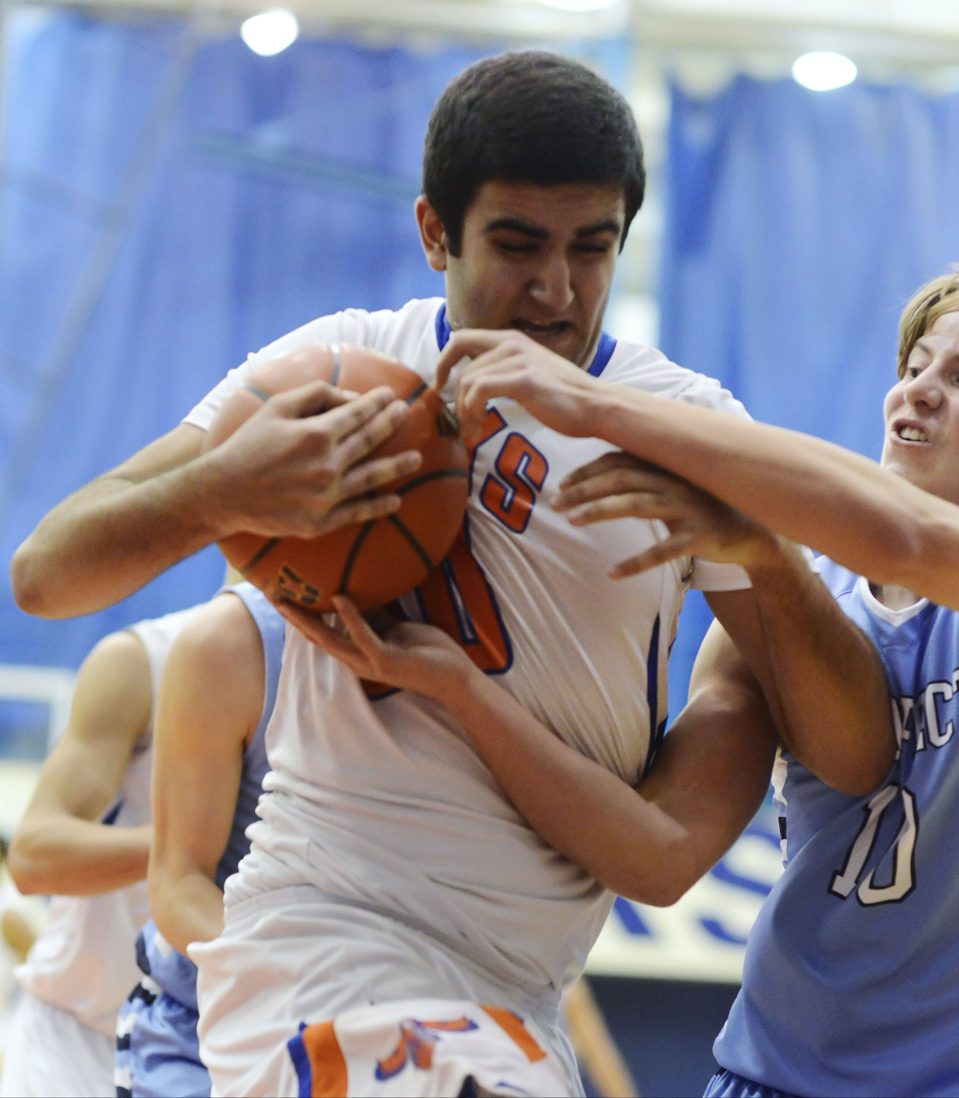 After grabbing a rebound, Hoffman Estates' Joe Biko tries to keep the ball from the grasp of Prospect's Nick Lazarz during Tuesday's game.