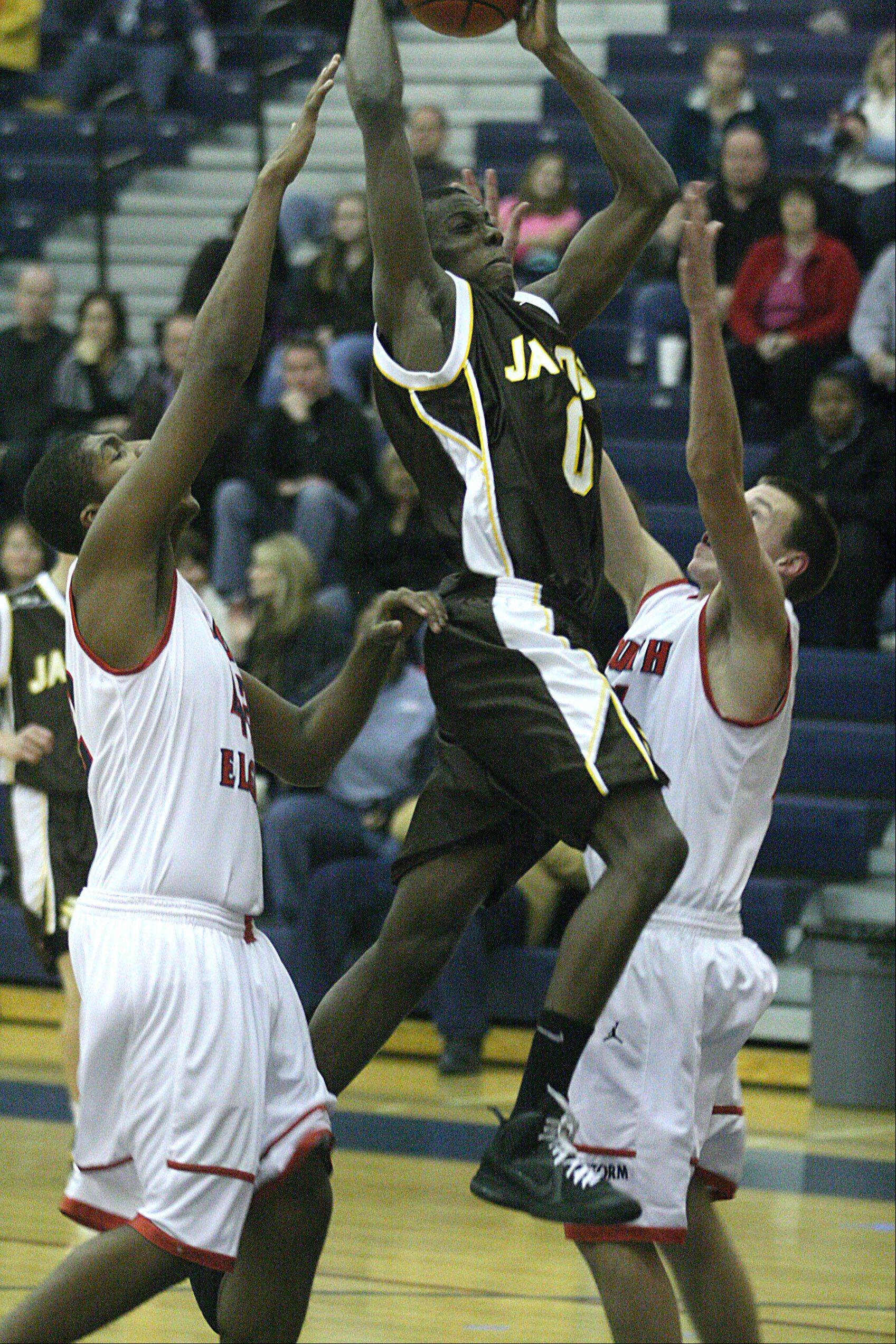 Jacobs' Lake Ojo, center, splits the defense of South Elgin's Robert Grant, left, and Brian Winsel, right.