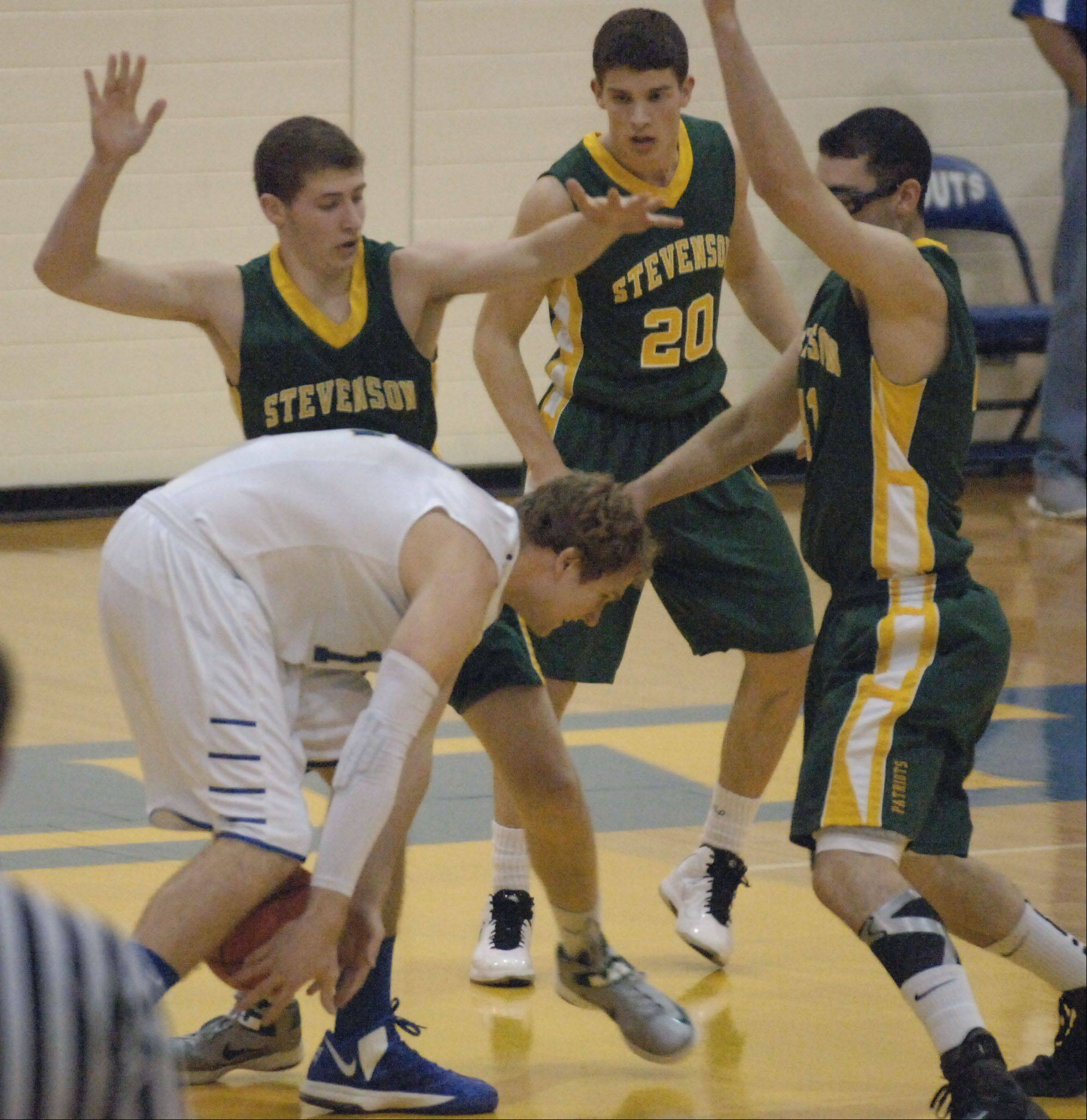 Lake Forest's Evan Boudreaux is pressured by Stevenson players from left Andrew Stempel, Matthew Morrissey, and Adam Cohen during Tuesday night's boys basketball game in Lake Forest.
