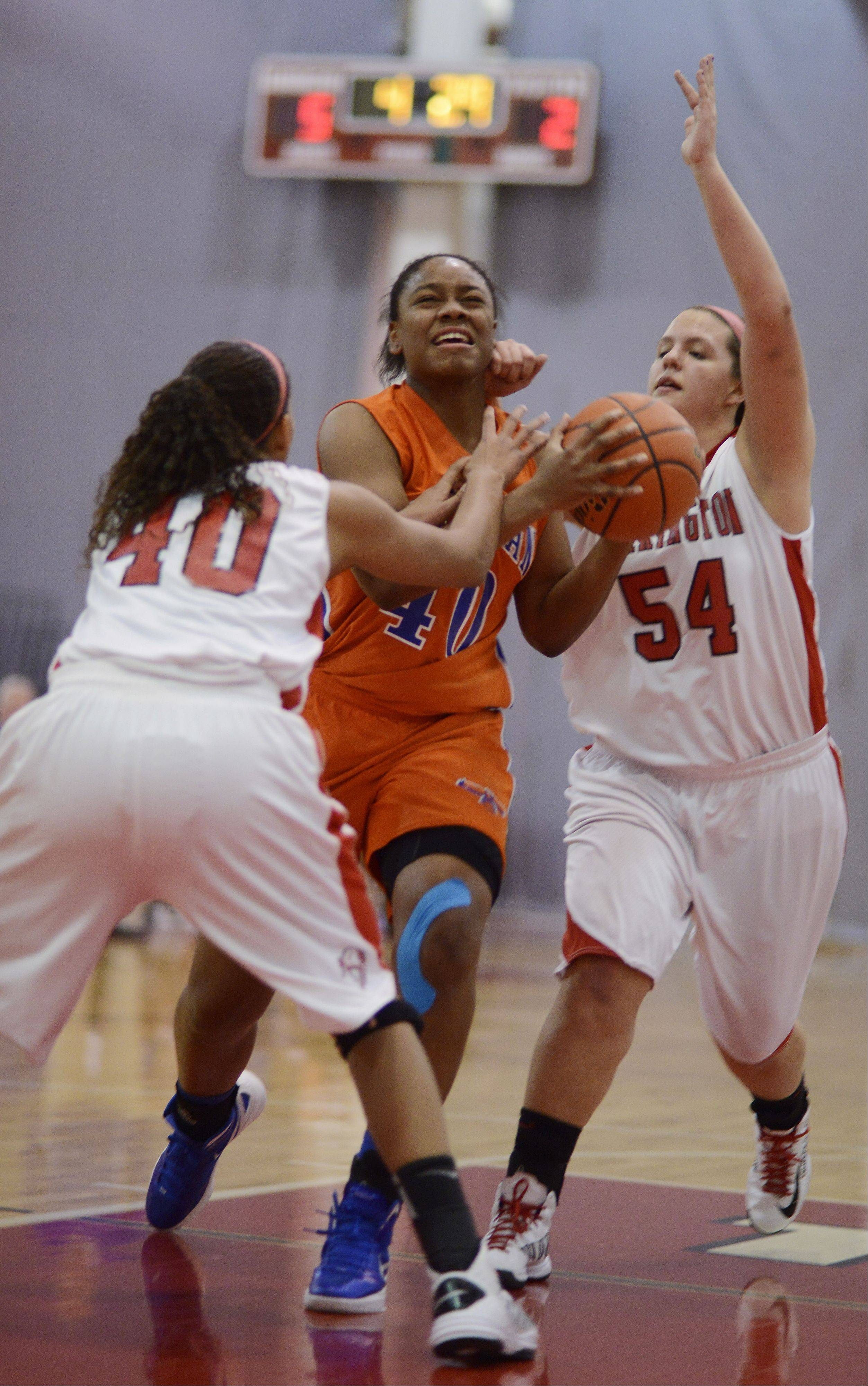 Hoffman Estates' Destinee Young, middle, draws contact as she drives to the basket against Barrington's Bryana Hopkins, left, and Alexa Resch during Wednesday's game.