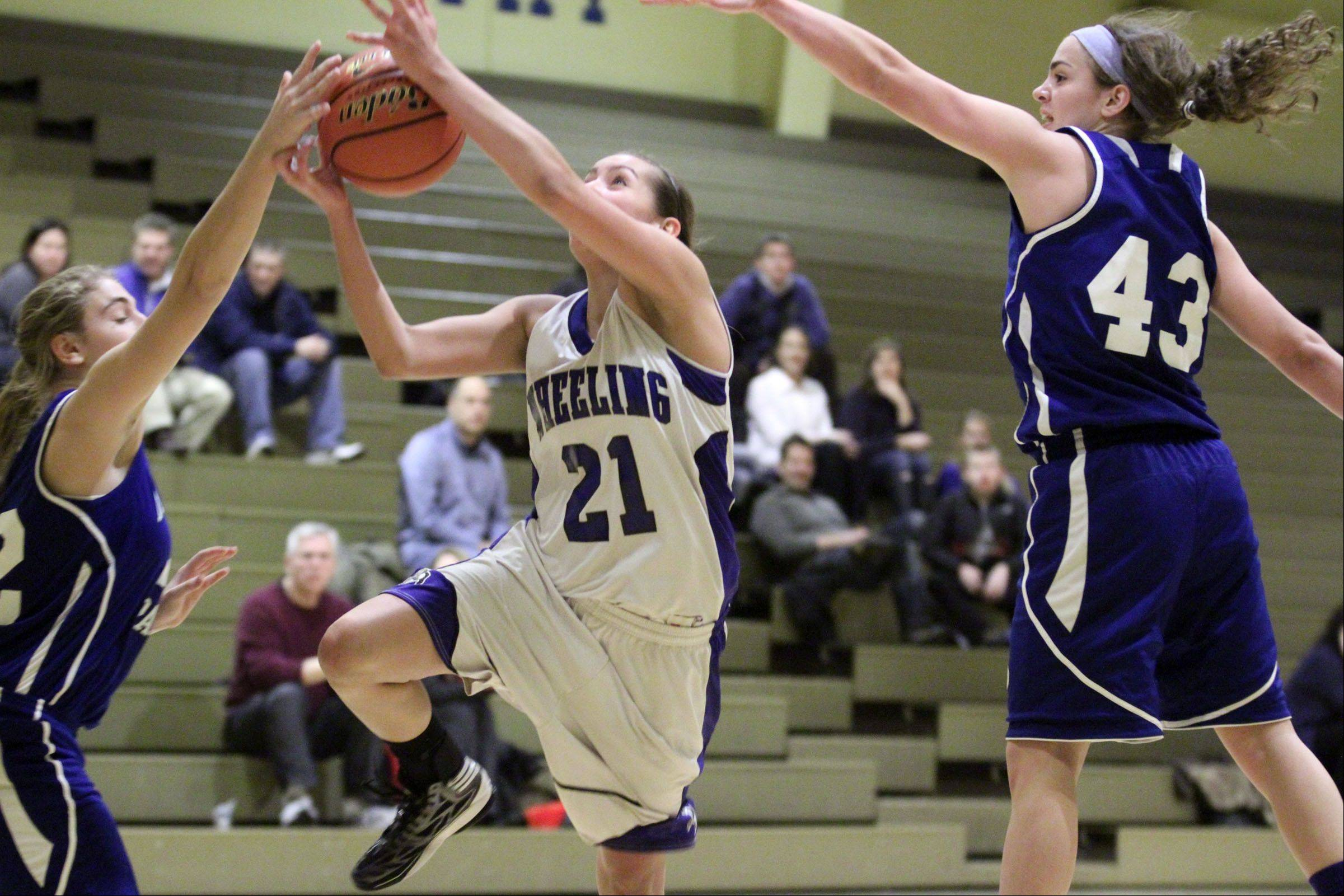 Wheeling's Deanna Kuzmanic drives the lane, splitting a pair of Highland Park defenders including Lena Munzer, right, for a layup at Wheeling on Thursday.