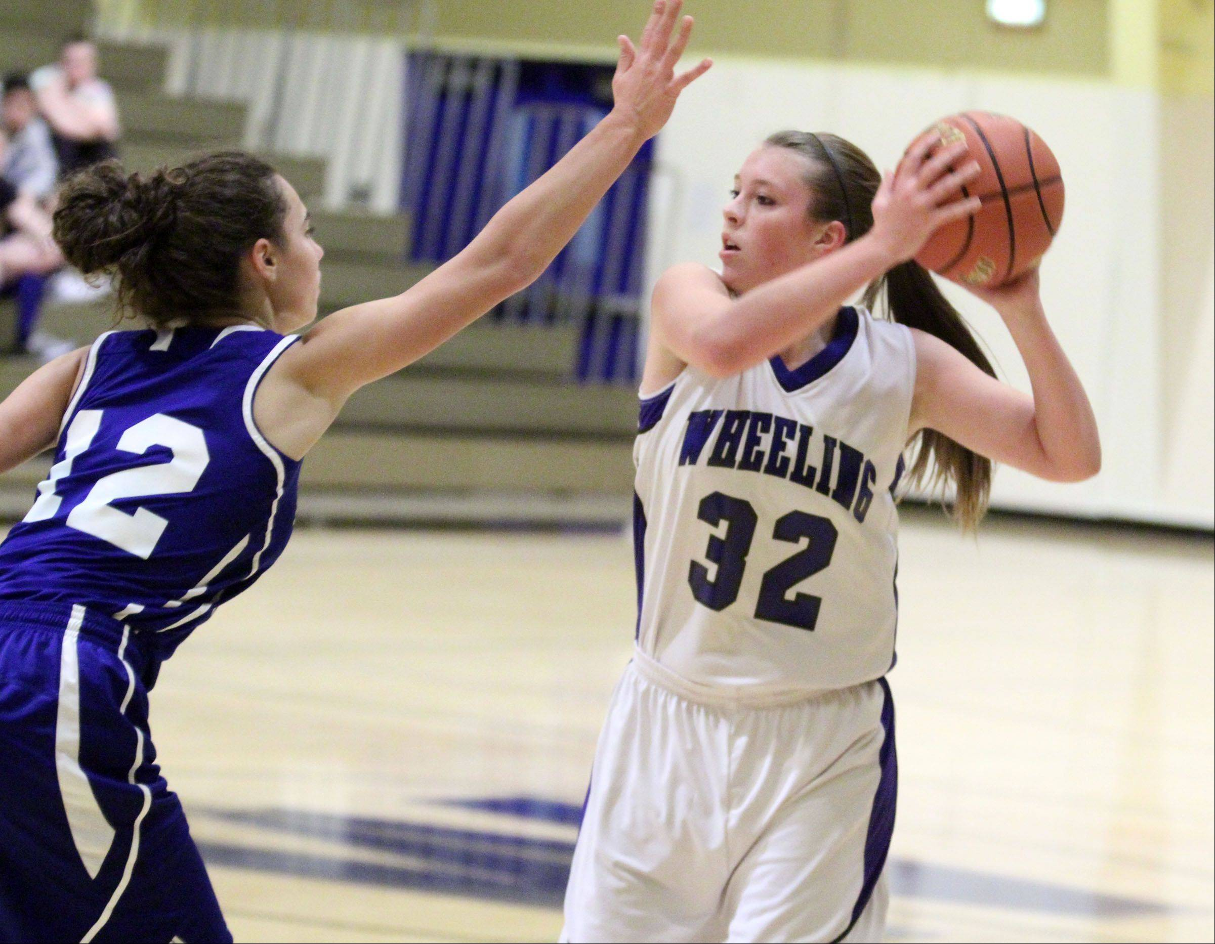 Wheeling's Brie Majkowski looks to pass over Highland Park defender Tina Berardi at Wheeling on Thursday.