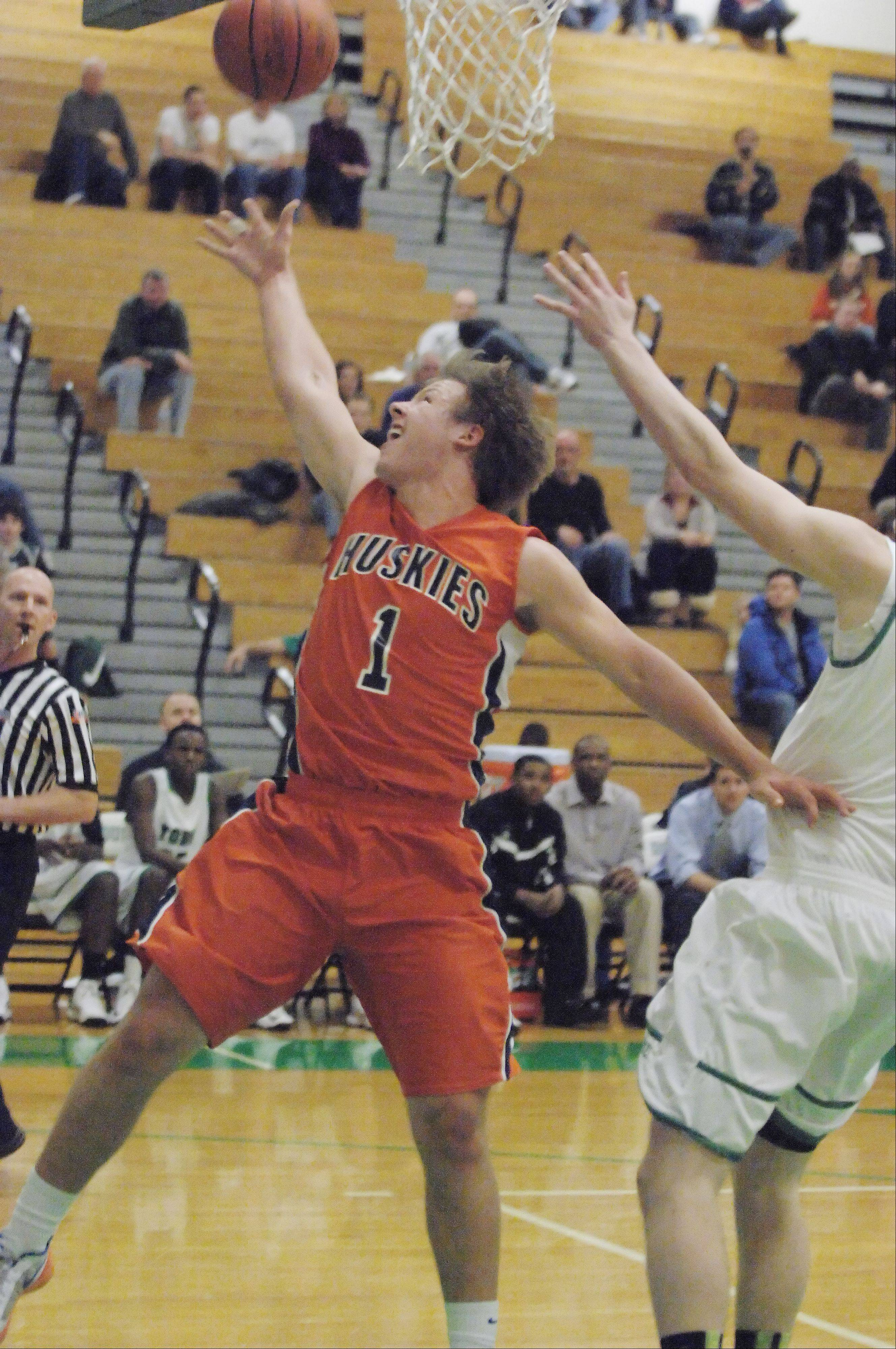 Derek Westman of Naperville North brings the ball to the net during the Naperville North vs. York boys basketball game Friday,