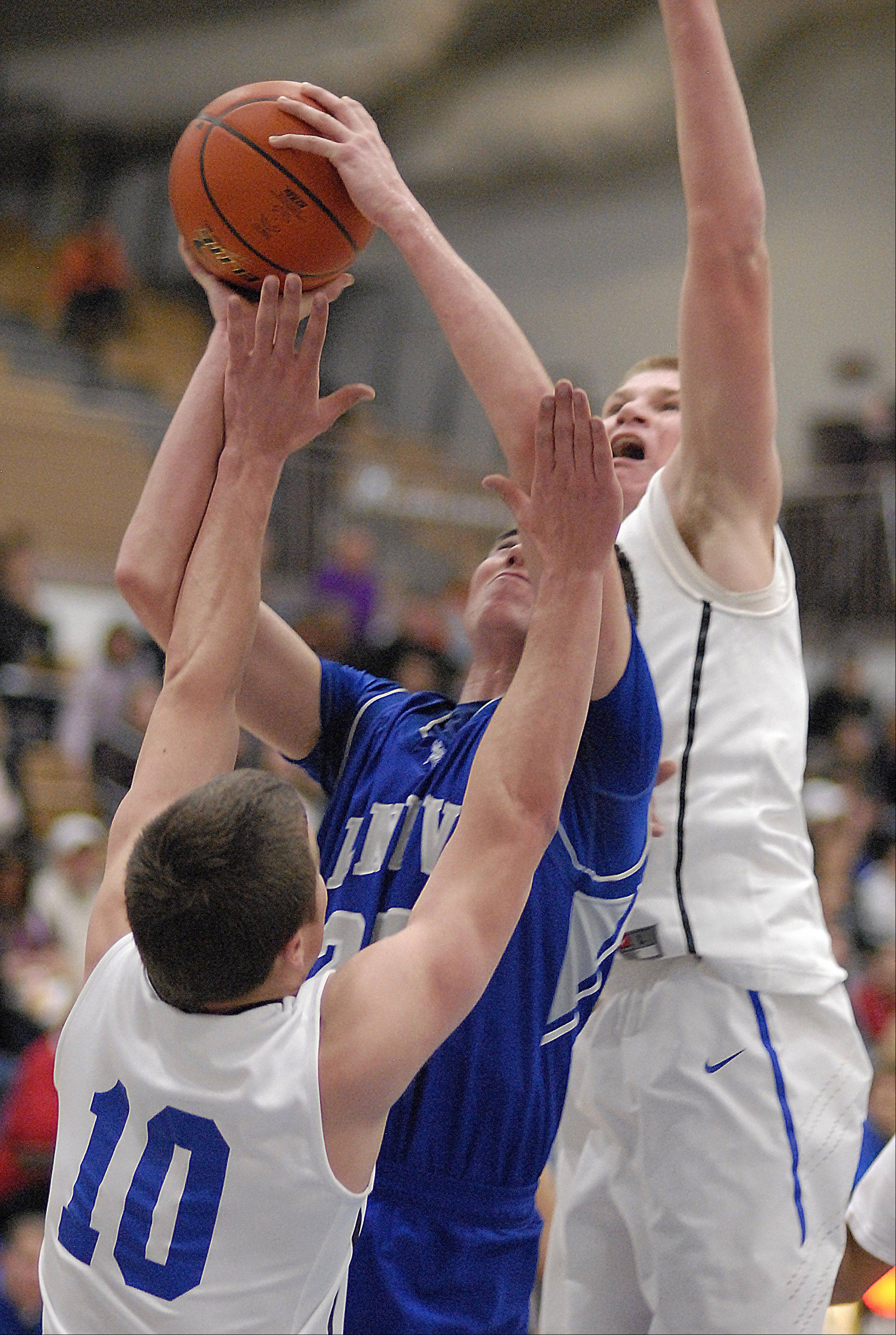 Geneva's Nate Navigato is swarmed under the hoop by St. Charles North's Ryan Thomas and Justin Stanko in the third quarter .