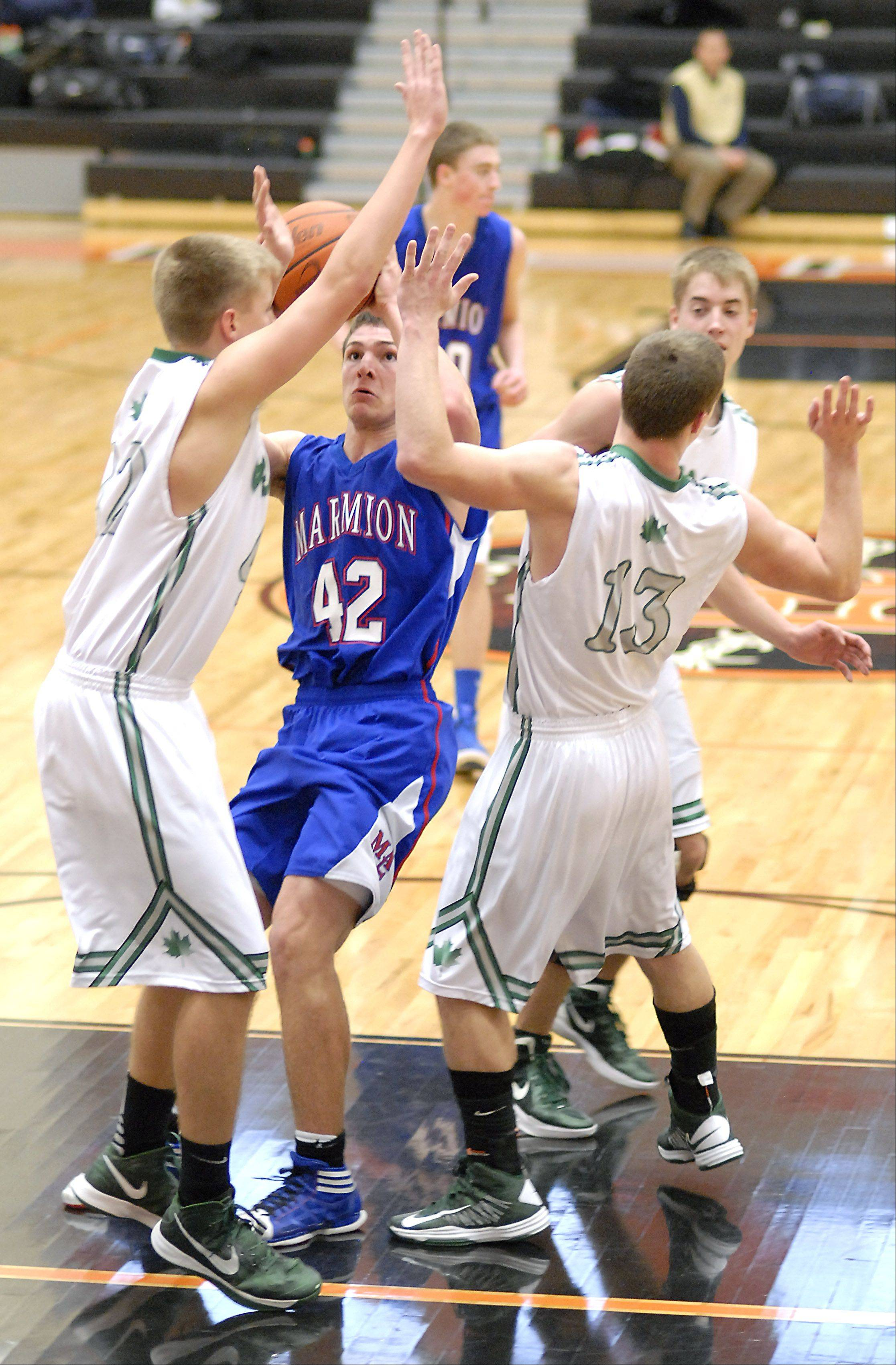 Marmion's Jordan Glasgow shoots past a block by Geneseo's Jake Scott and Luke Snyder in the third quarter of the DeKalb tournament on Saturday, December 22. 30