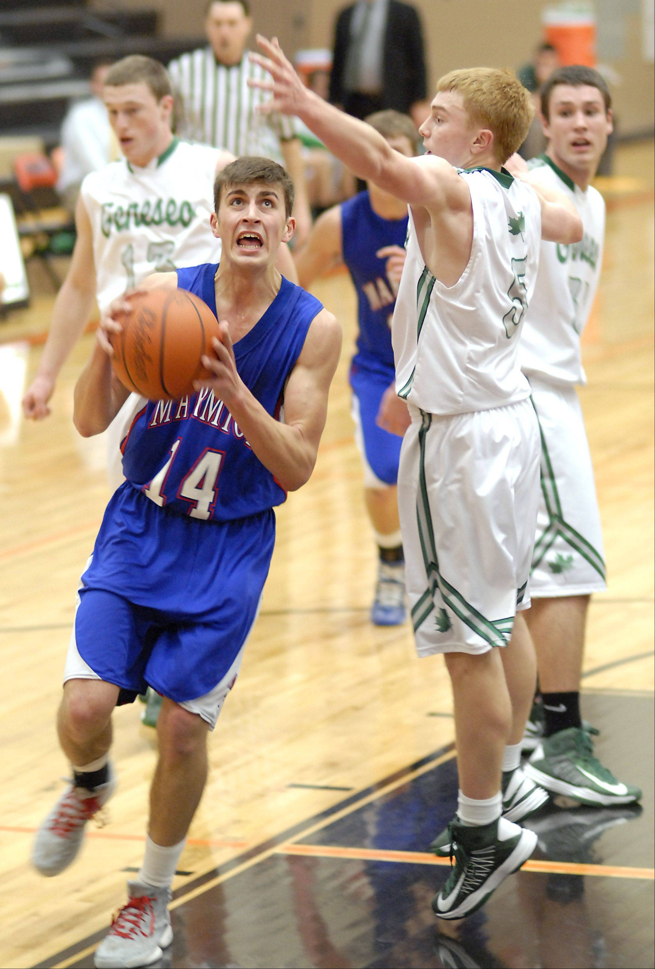Marmion's Alex Theisen shoots past a block by Geneseo's Jordan Starkey in the fourth quarter of the DeKalb tournament on Saturday, December 22.
