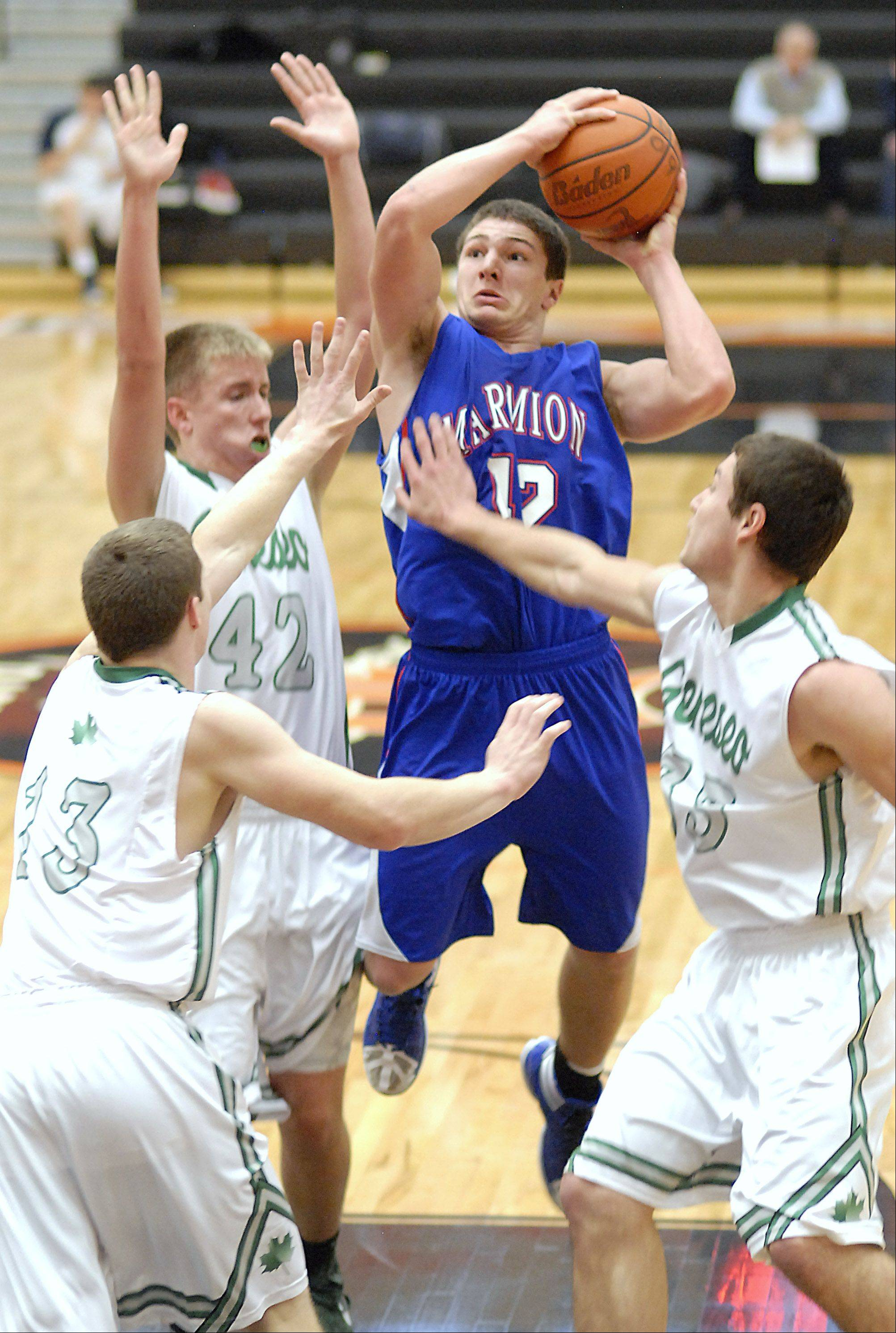 Marmion's Jordan Glasgow shoots over a team block by Geneseo's Luke Snyder, Jake Scott and Austin Lindstrom in the third quarter of the DeKalb tournament on Saturday, December 22.