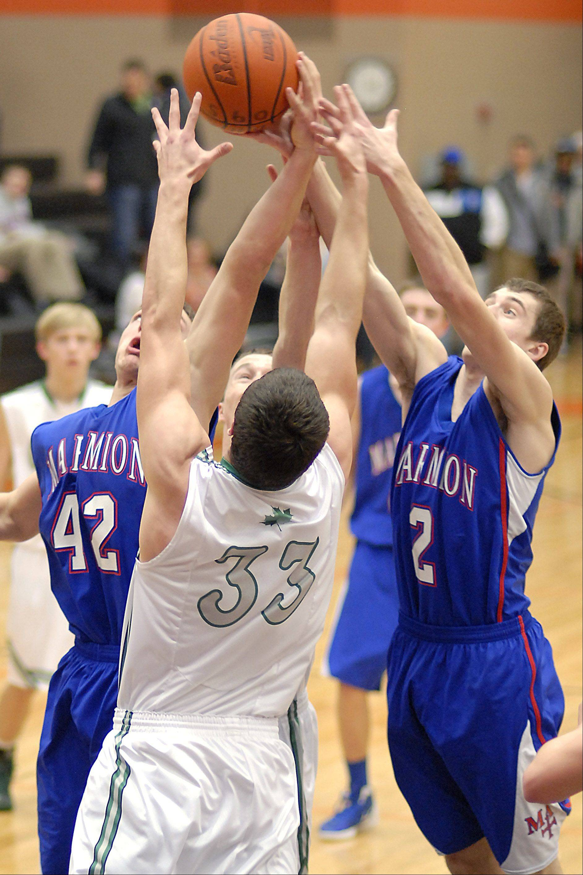 Marmion's Jordan Glasgow and Jake Ruddy leap for a rebound with Geneseo's Grant Burress in the first quarter of the DeKalb tournament on Saturday, December 22.