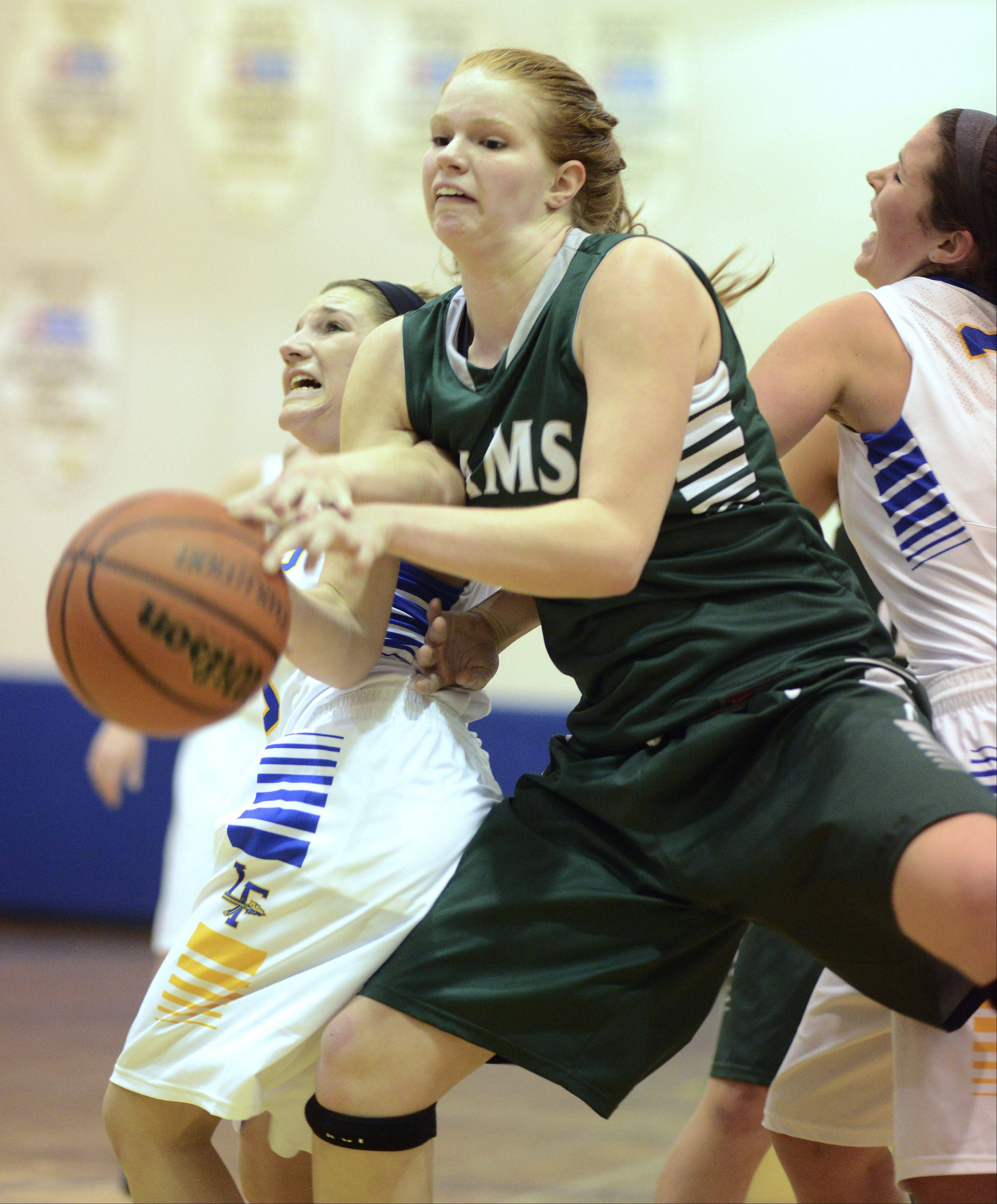 Grayslake Central's Morgan Dahlstrom, middle, draws contact while driving through Lake Forest's Gabby Perino, left, and Annie Keller during Saturday's game at Warren.