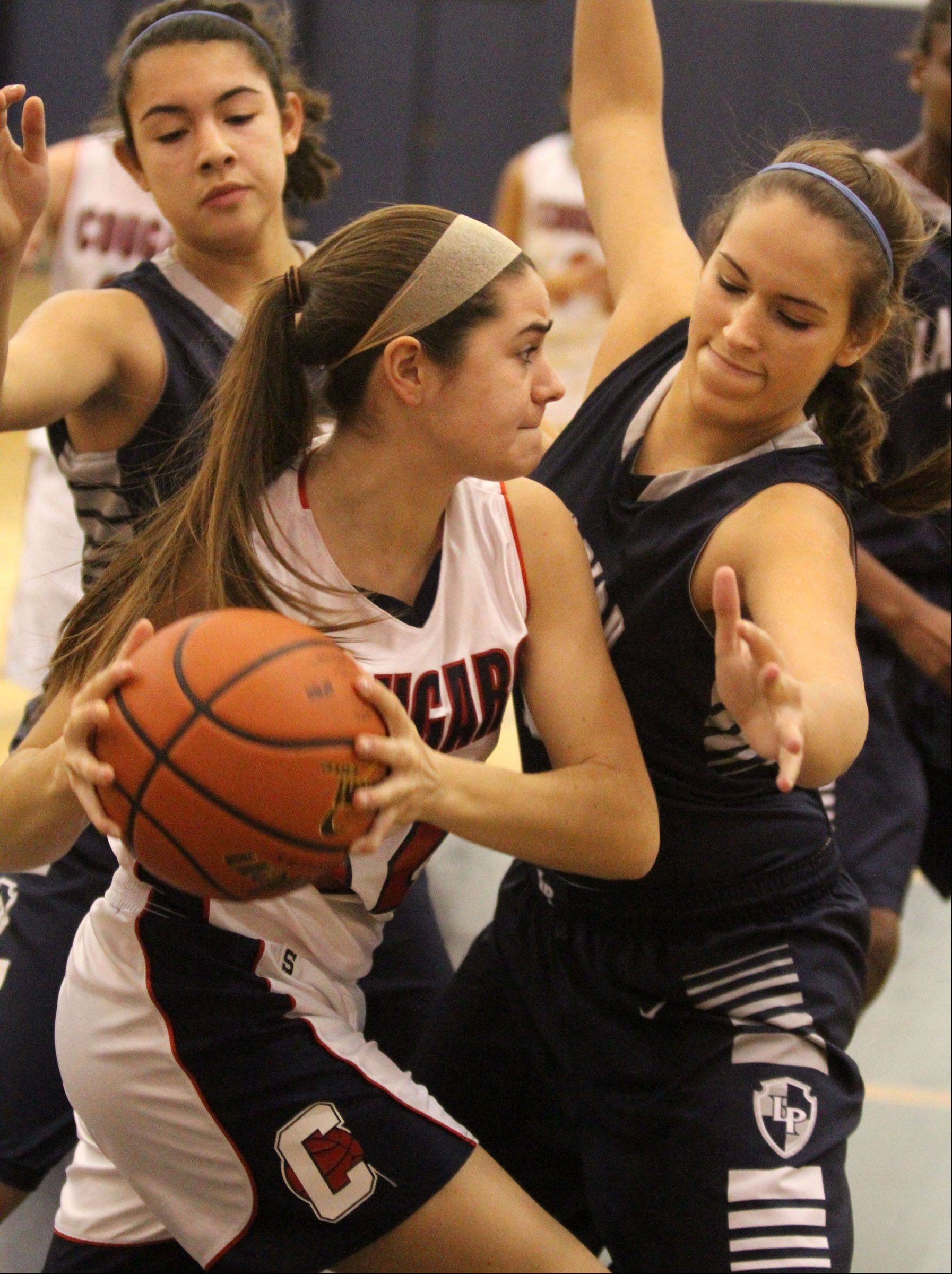 Conant's Morgan Retzer looks to pass the ball while sandwiched between Lake Park defenders Maria Zepeda, left, and Kaley Noonan on Saturday.