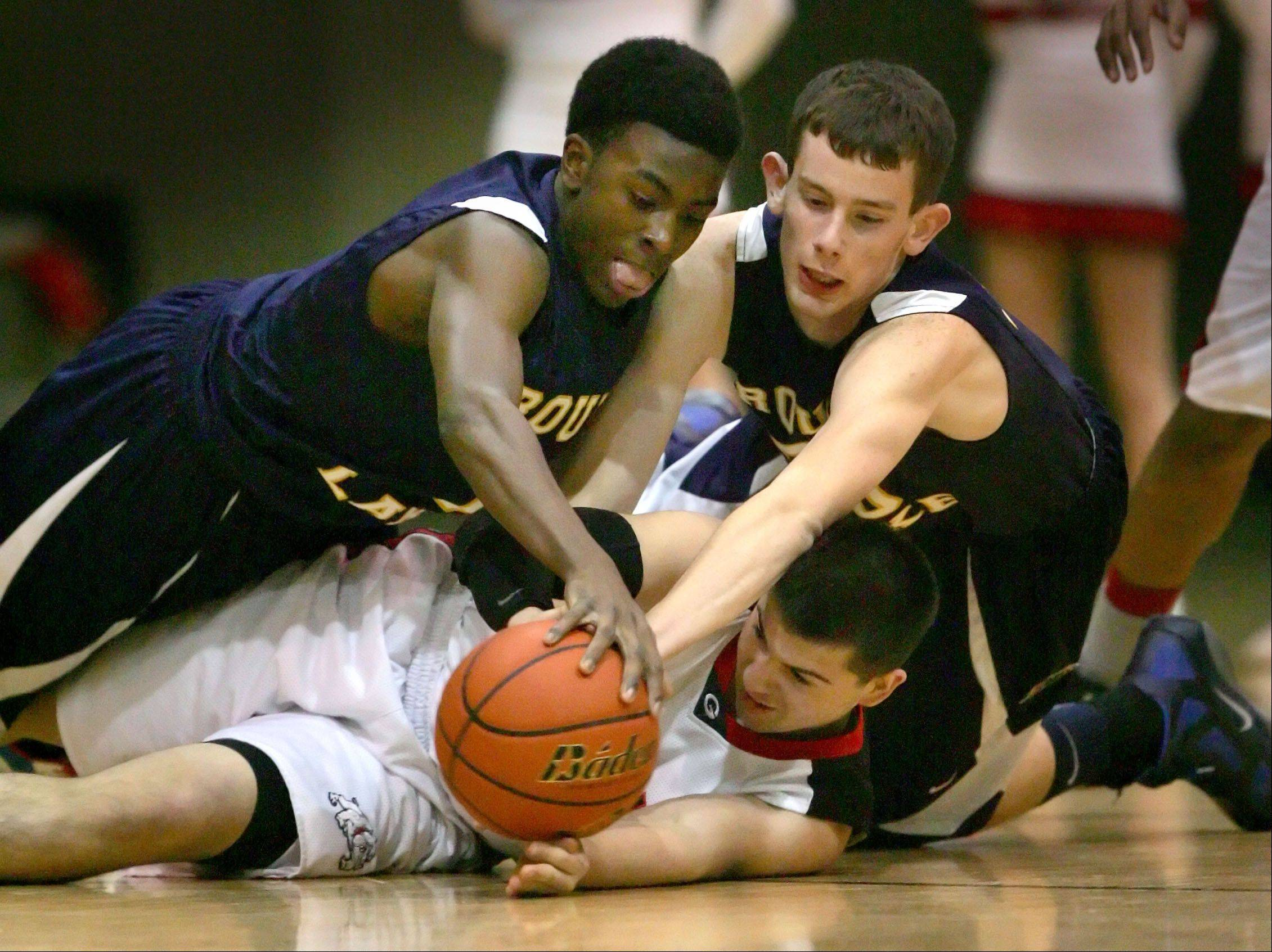 Round Lake's Karnell Wright, left, and Zack Pick battle for a loose ball with Grant's Luke Lostroscio Wednesday night at Grant High School.