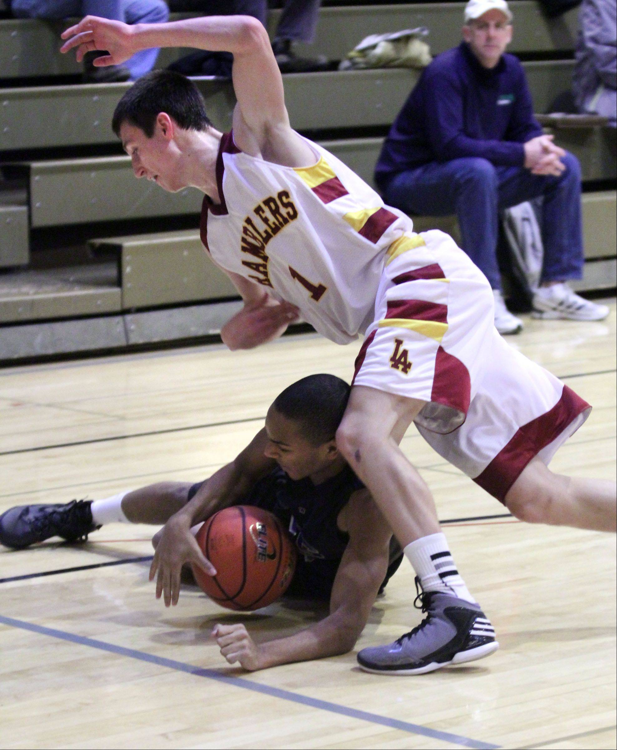 Loyola defender Kevin Kucera falls over Wheeling's Nate Laude after a battle for a loose ball in Wheeling on Wednesday.