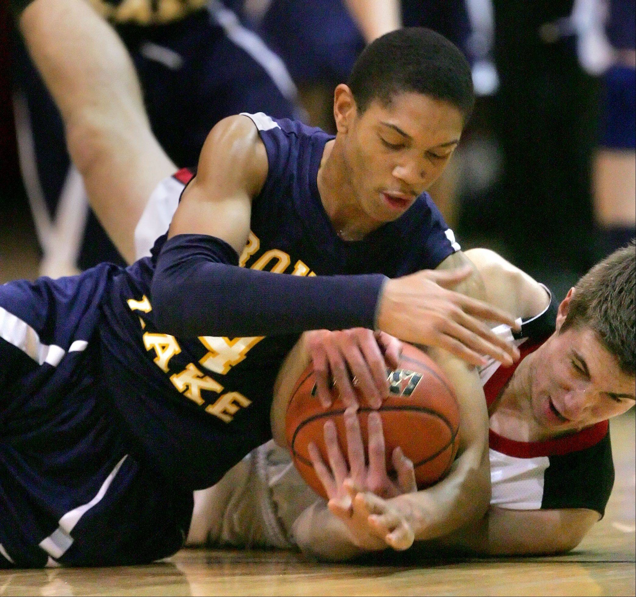 Round Lake's Rayshawn Bommon, left, and Grant's Matt Malmberg battle for a loose ball during their game Wednesday night at Grant High School.