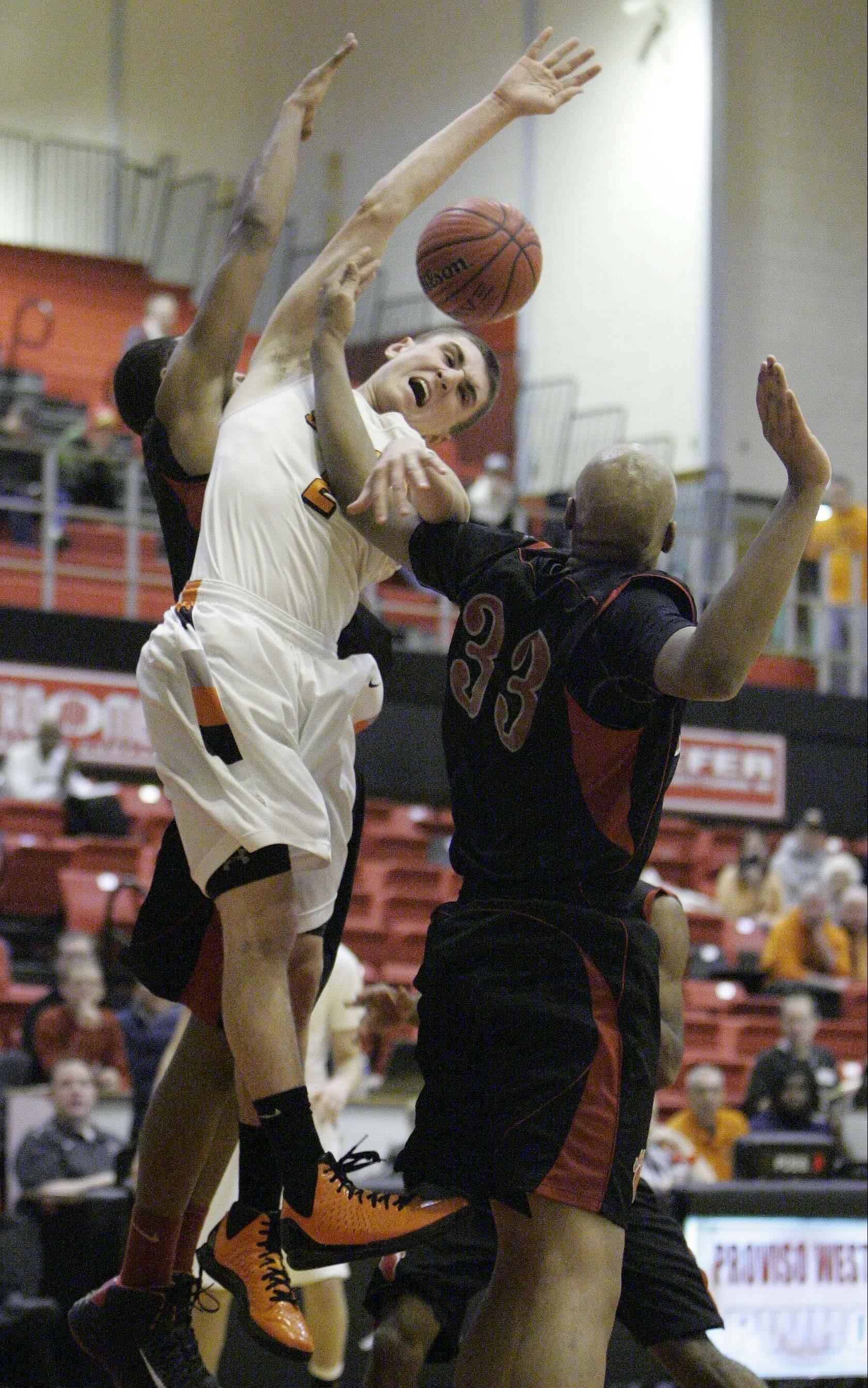 St. Charles East's Dom Adduci is fouled by Von Steuben's Malachi Matias, 33, Wednesday at the Proviso West Holiday Tournament in Hillside.