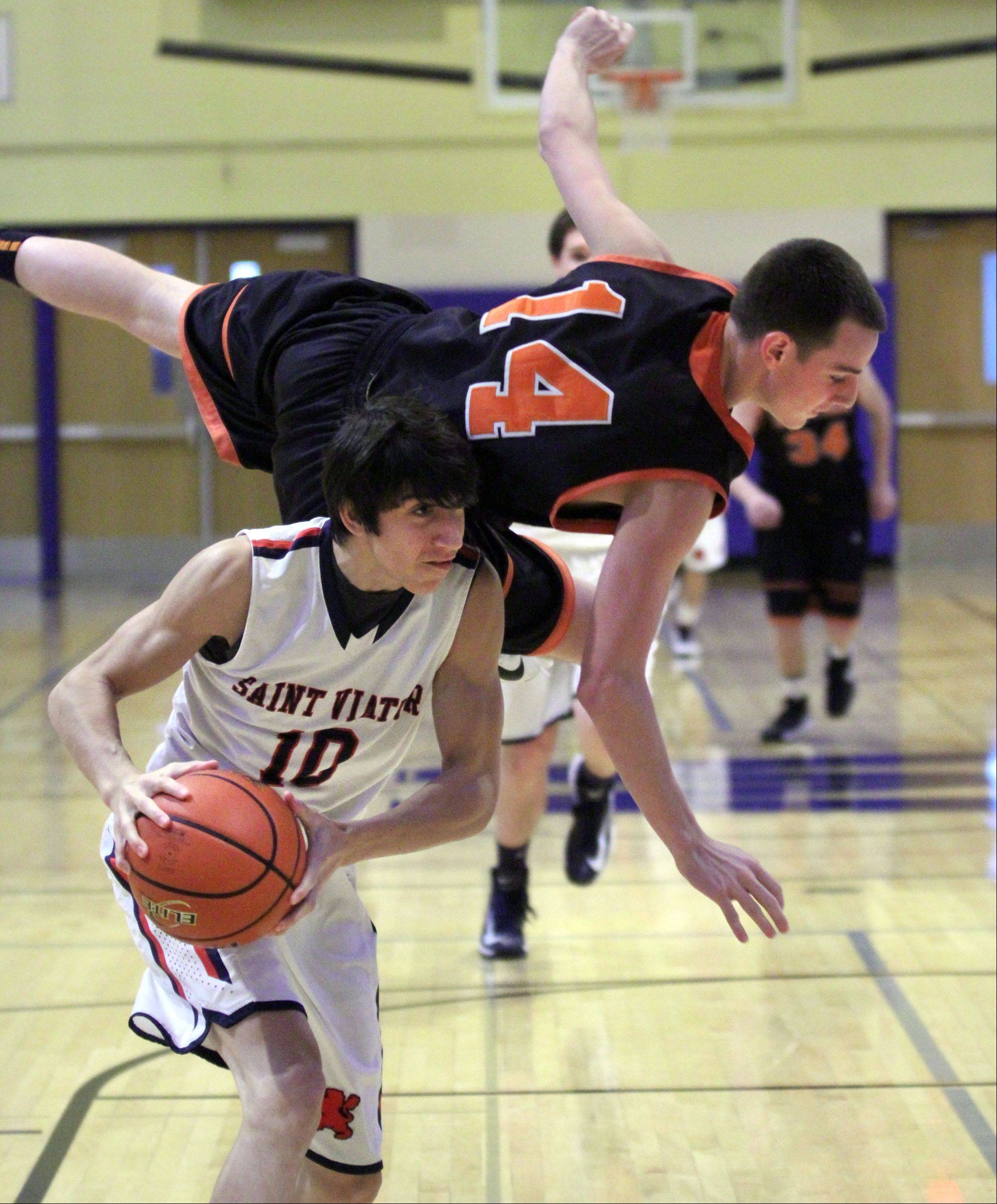 While trying to block a shot Libertyville defender, Drew Cayce falls over the back of St. Viator's Robert Grant at the 35th annual Hardwood Classic in Wheeling on Wednesday.