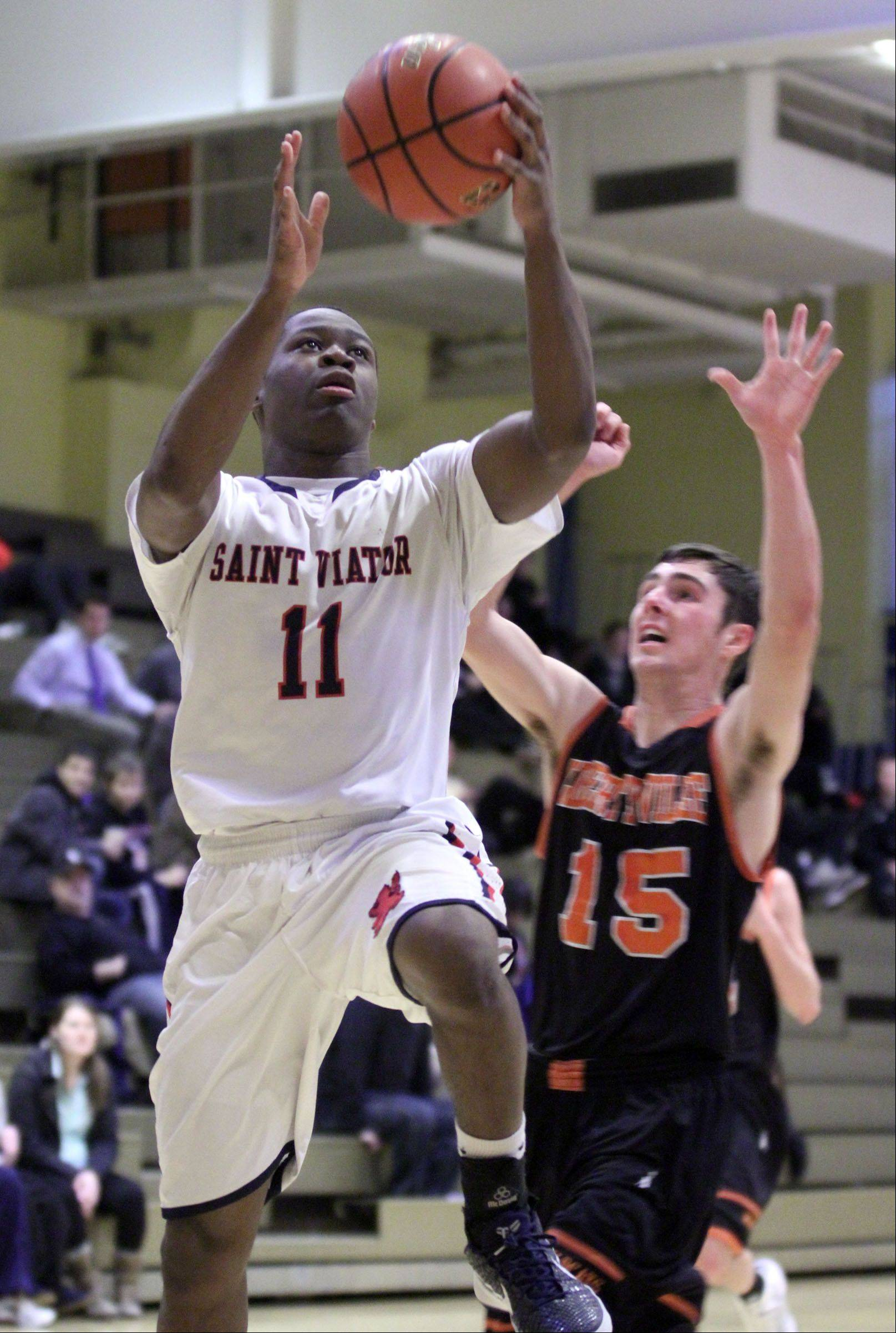 St. Viator's Mayo Arogundade puts the ball up against Libertyville defender Matt Reed on Wednesday in Wheeling.