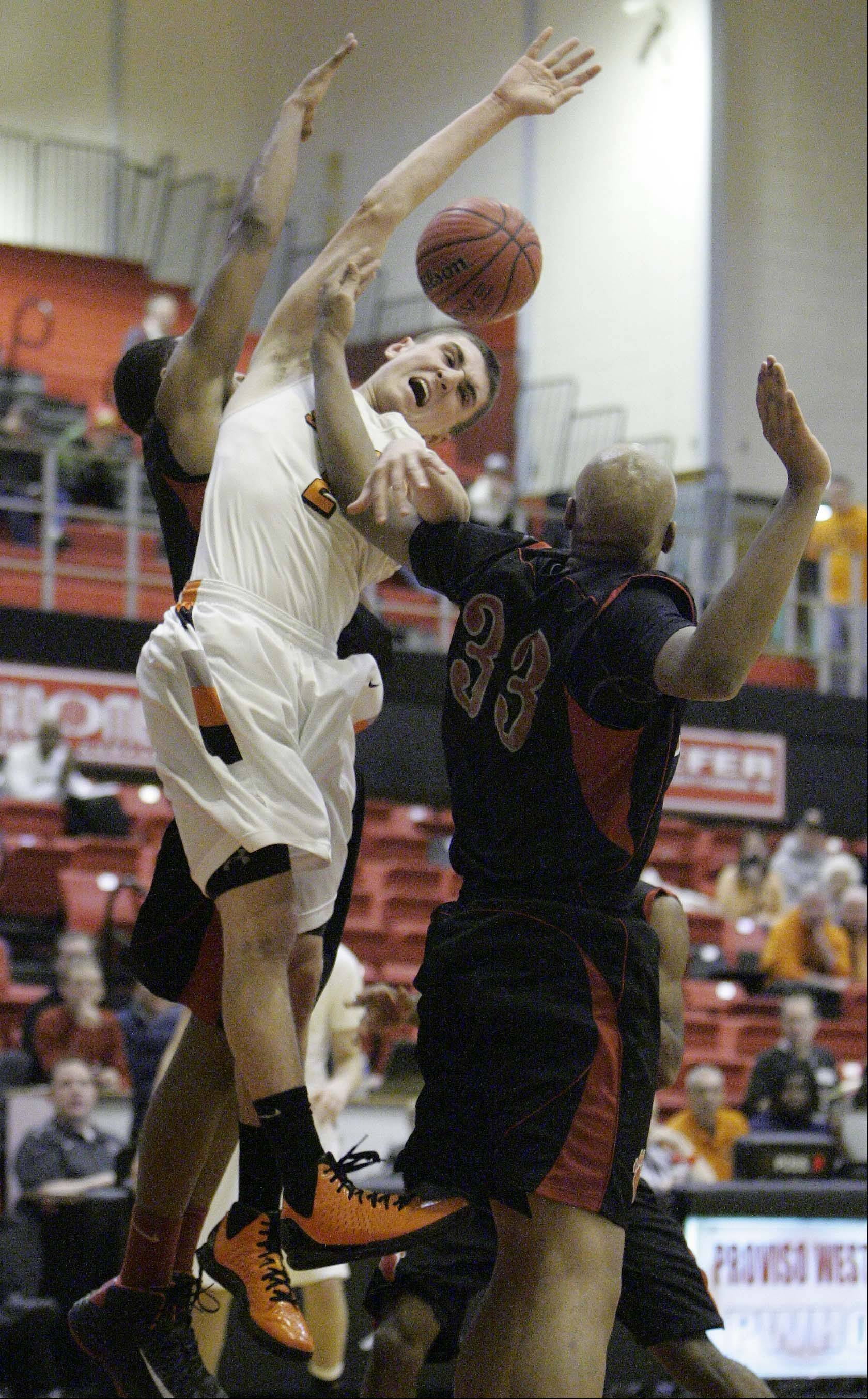 St. Charles East's Dom Adduci, 2, goes to the hoop past Von Steuben's Malachi Matias, 33, at the Proviso West Holiday Tournament in Hillside, Wednesday December 26, 2012.