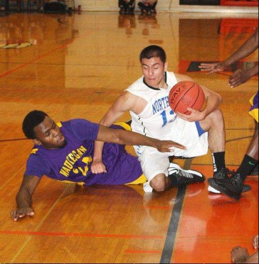 St. Charles North's Tony Neari battles Waukegan's Quintin Davis for a loose ball Thursday at the Pontiac Holiday Tournament.