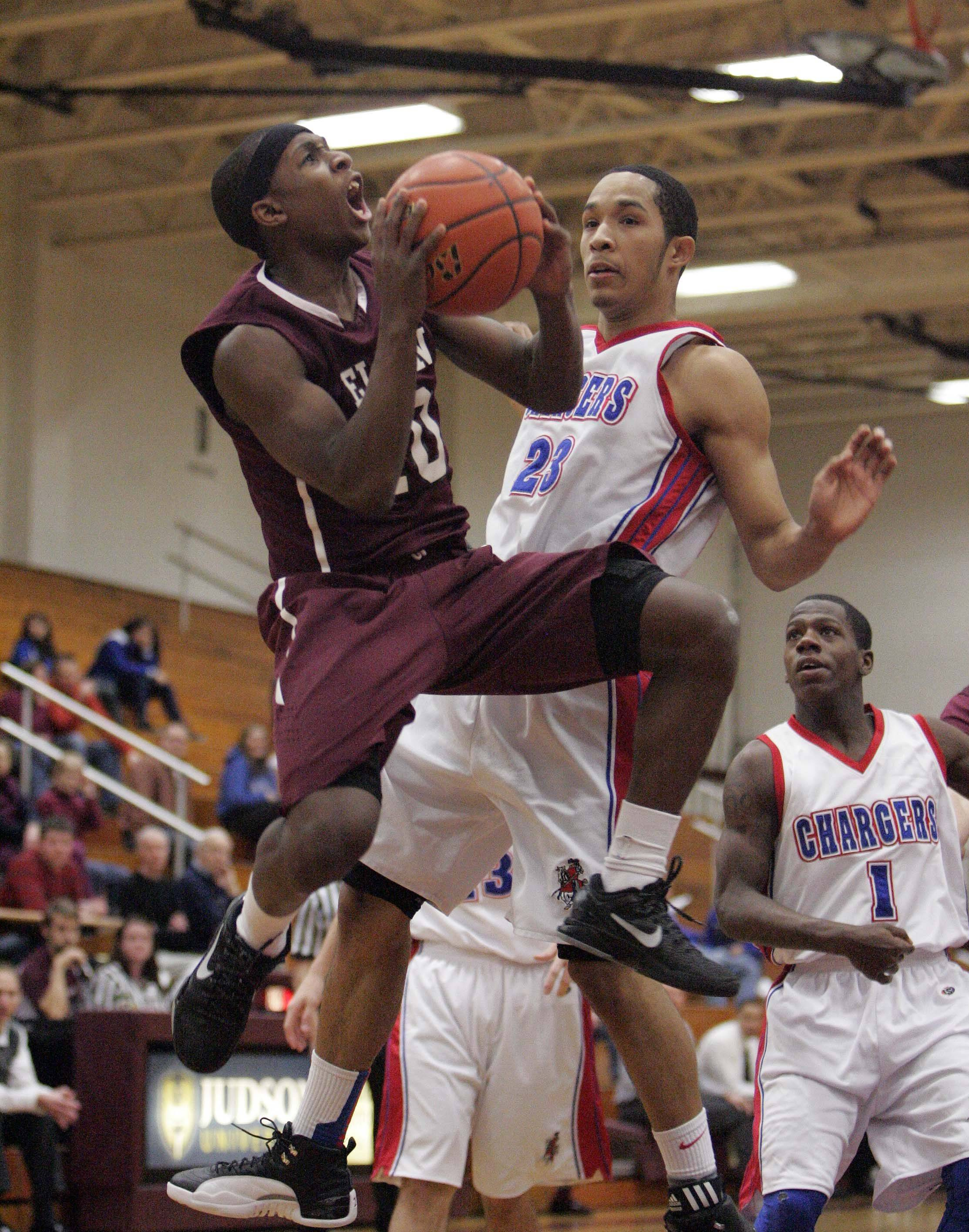 Elgin senior Arie Williams puts up a shot that would score the 1,000th point of his career during the Maroons' 53-52 win over Dundee-Crown at the Elgin Holiday Tournament Thursday night. Defending is Dundee-Crown's Cordero Parson (21).