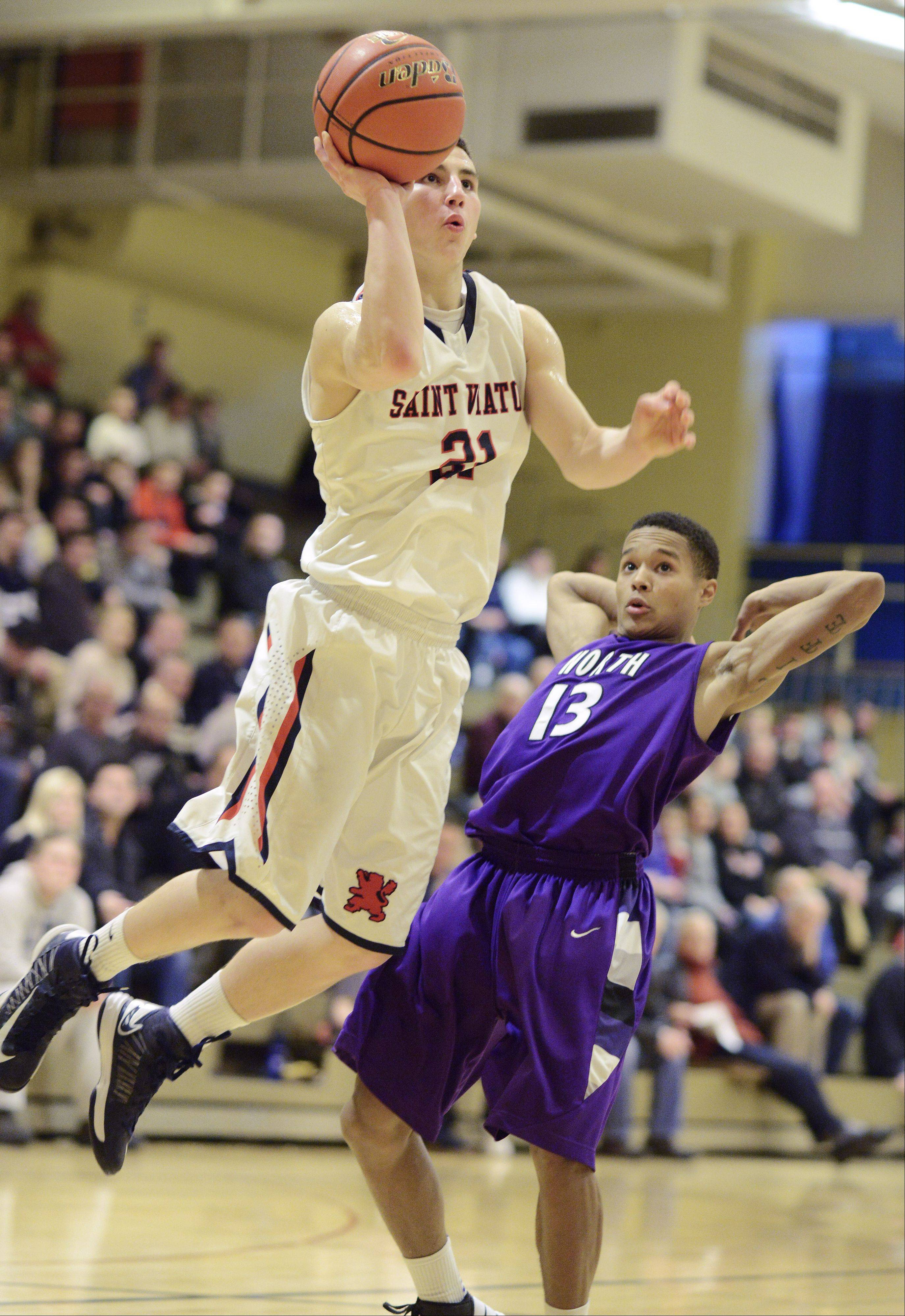 St. Viator's Mark Falotico takes a jump shot as he moves past Niles North's JJ Myles during Friday's semifinal of the Wheeling Tournament.
