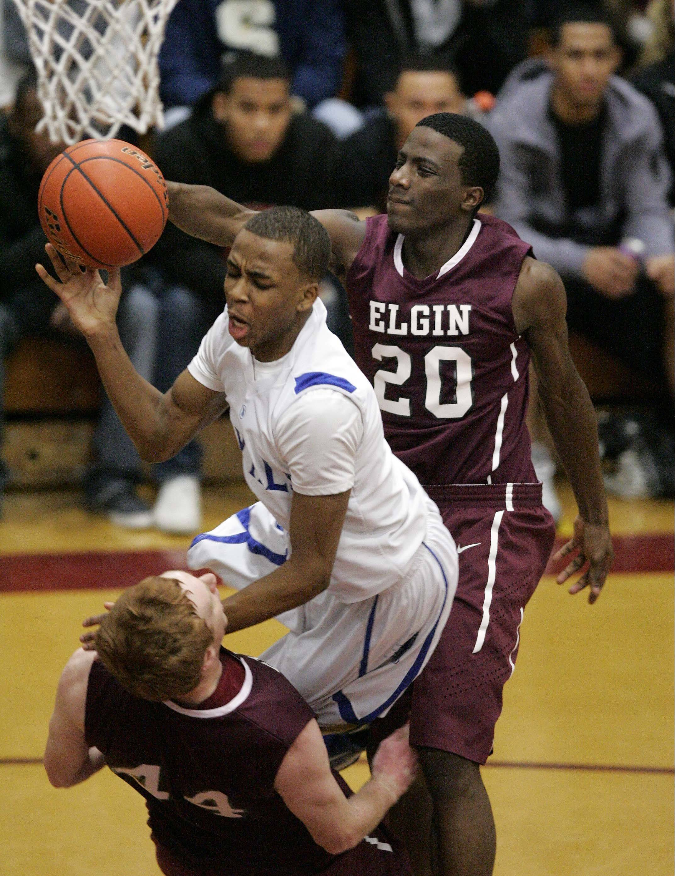 Larkin's Quantice Hunter (1) goes hard to the hoop as Elgin's Eric Sedlack stands strong during the championship game of the Elgin Holiday Tournament Saturday.