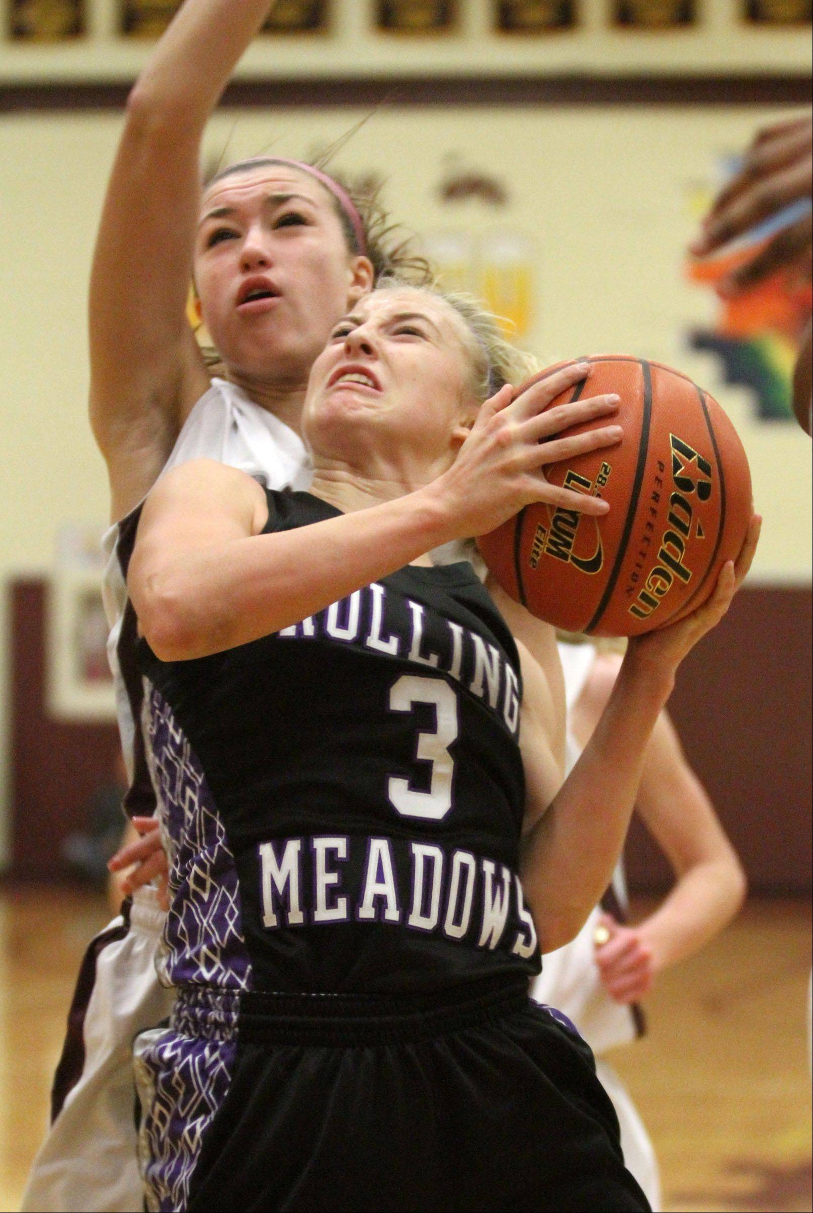 Rolling Meadows' Jackie Kemph shoots against Montini defender Kelsey Bogdan, left, in the championship game of the Montini holiday tournament in Lombard Saturday.