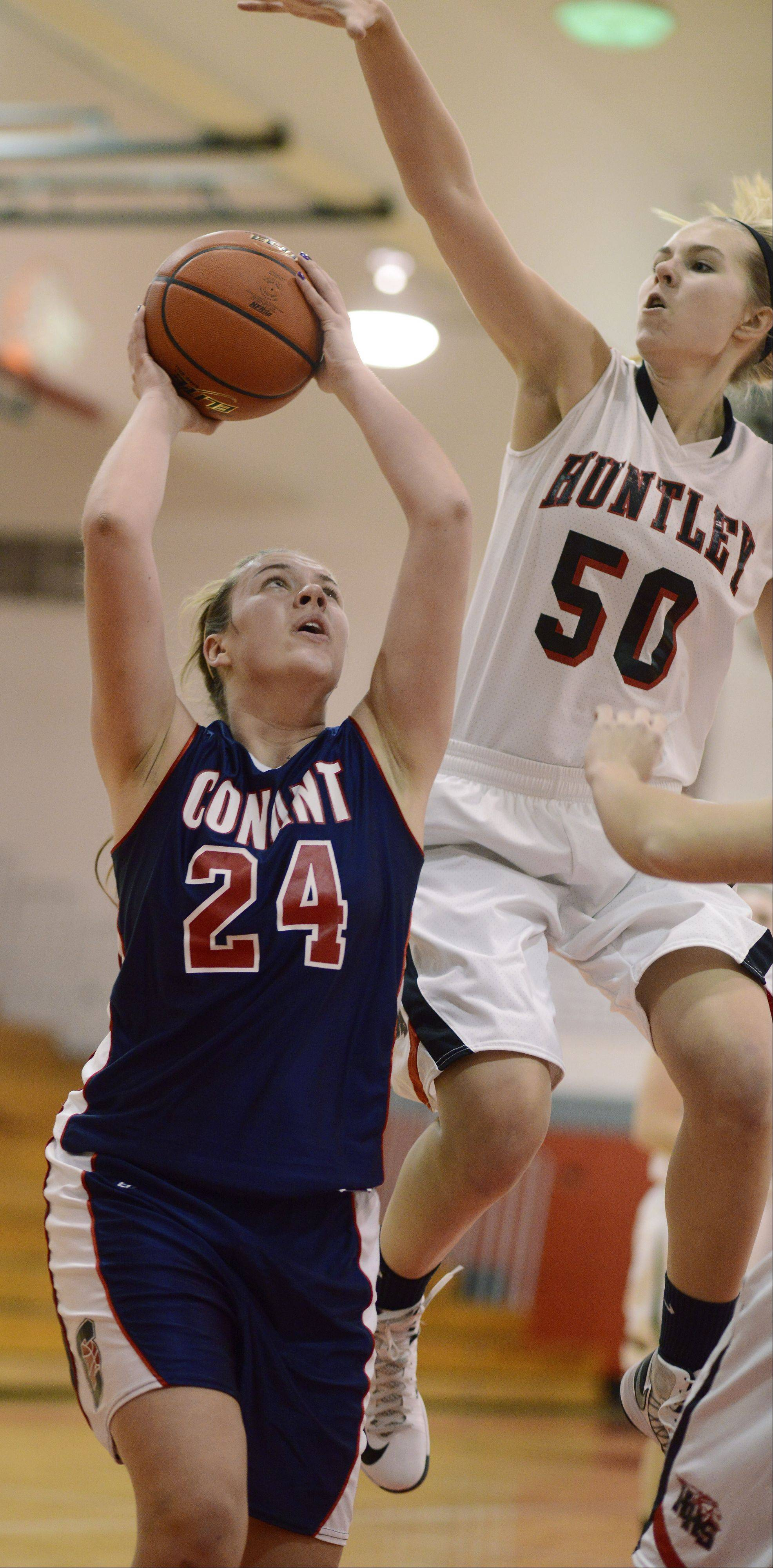 Conant's Haley Anderson, left, takes a shot under the basket as Huntley's Ali Andrews attempts a block during Saturday's game at Mundelein.