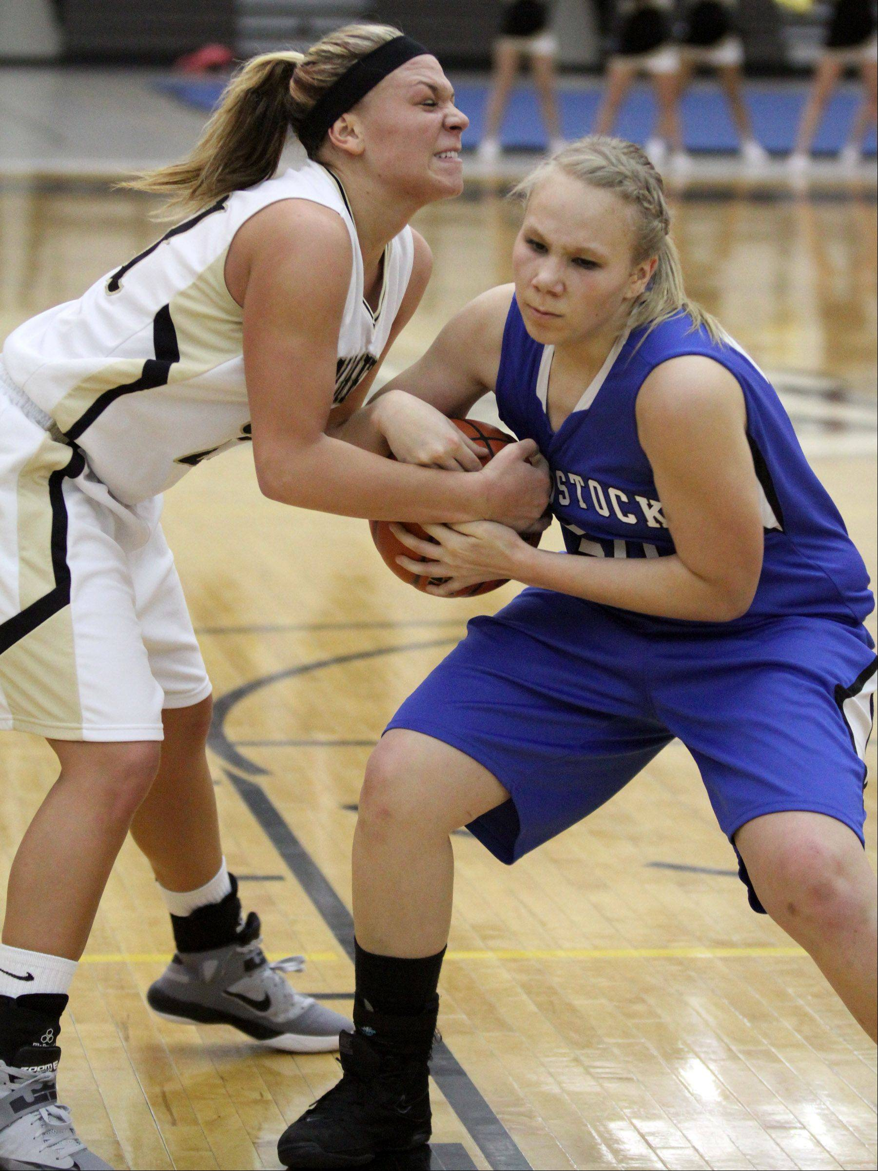 Grayslake North's Shyanne Ludwick fights for the ball with Woodstock's Ari Davis.