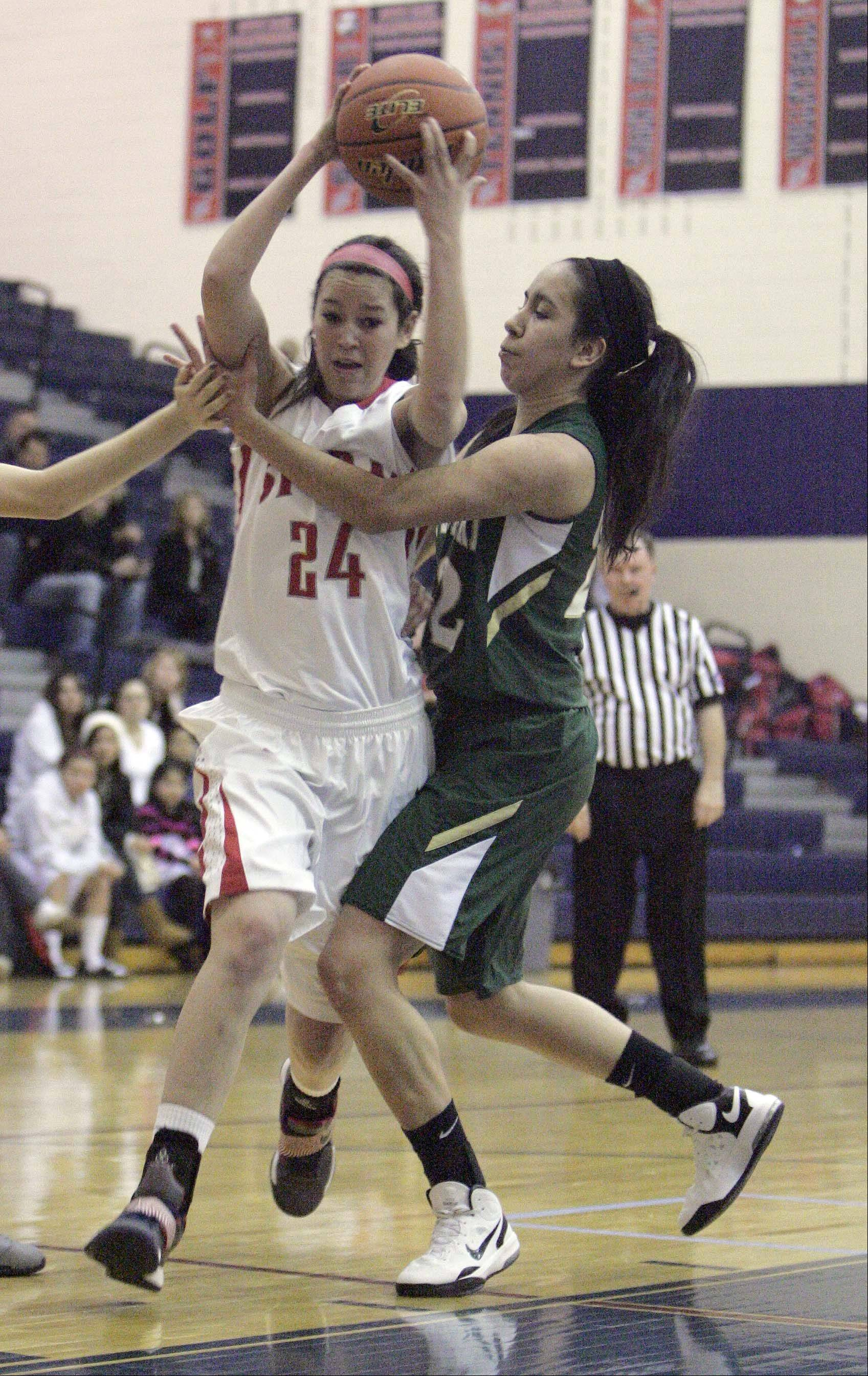 South Elgin's Kennede Miller (24) goes to the hoop as St. Edward's Clarissa Ramos defends Saturday at South Elgin.