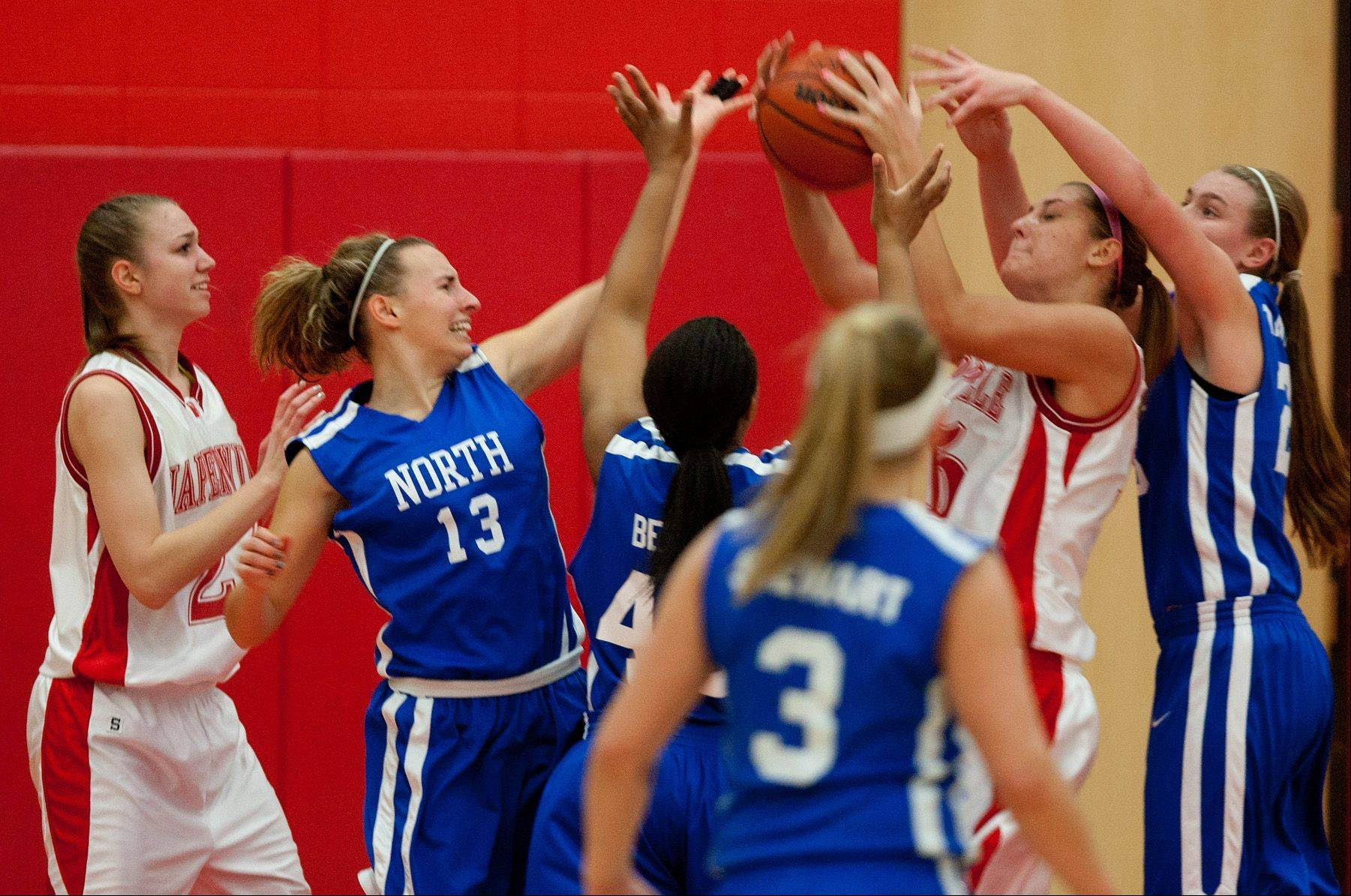 Naperville Central's Victoria Trowbridge grabs a defensive rebound over Wheaton North, during girls basketball action in Naperville.