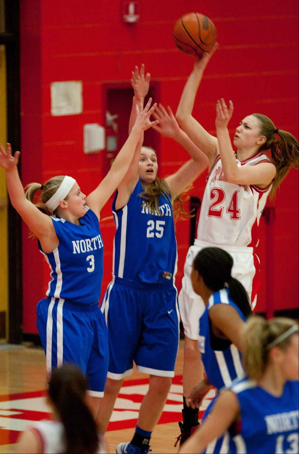 Naperville Central's Jamie Cuny (24), eyes the rim over Wheaton North, during girls basketball action in Naperville