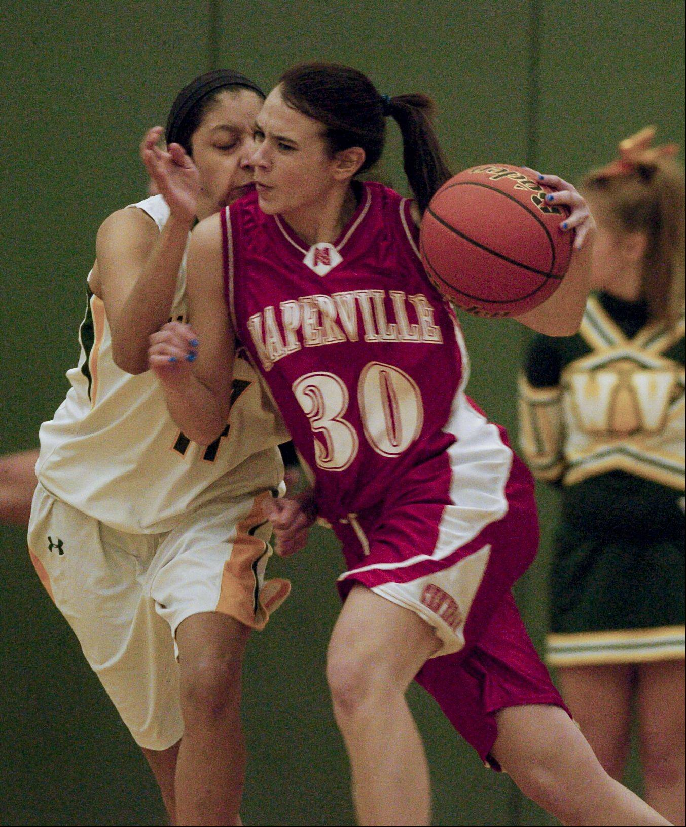 Shannon Ryan of Naperville Central drives past Andrea Colin of Waubonsie Valley.