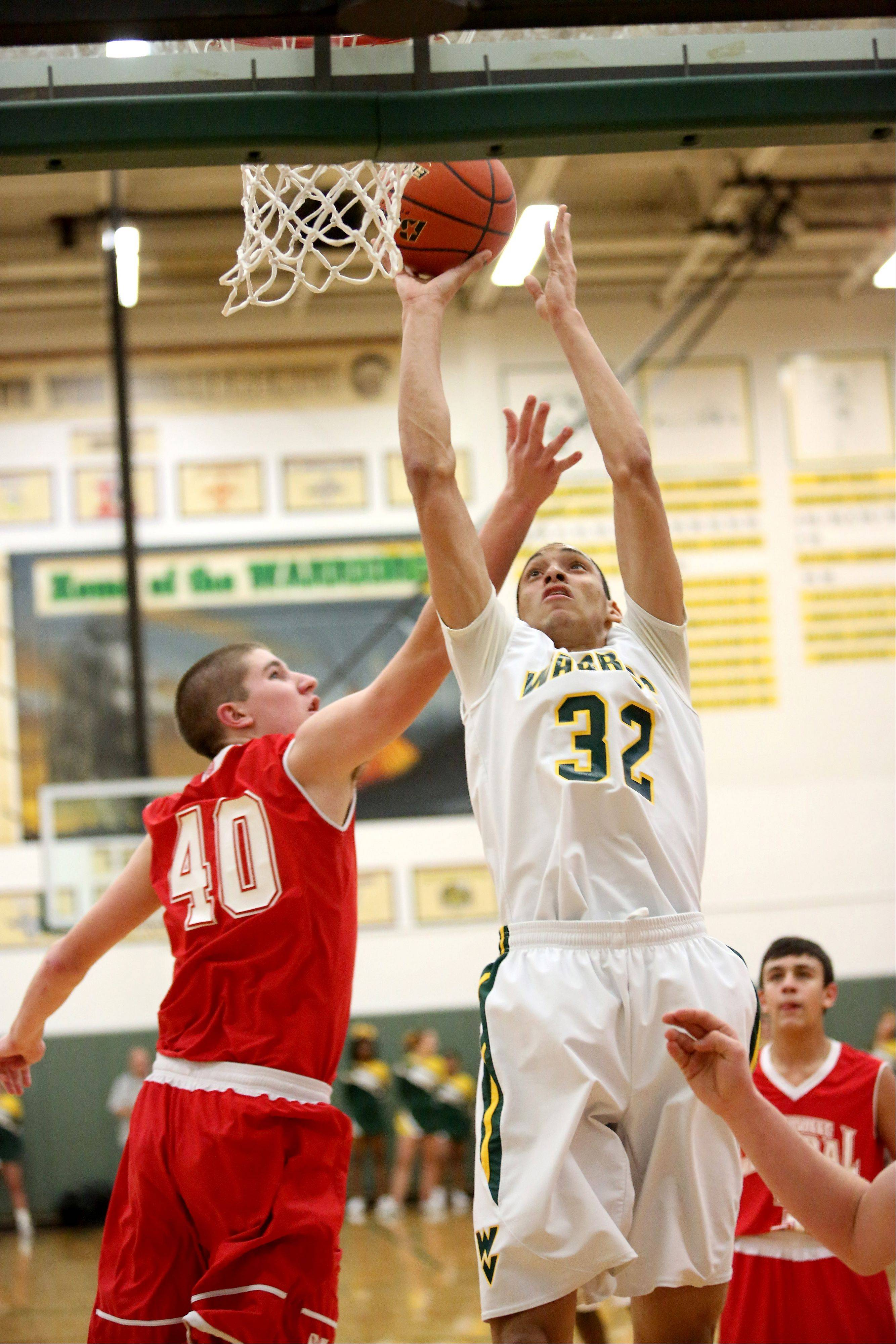 Bryan Jefferson of Waubonsie Valley goes up for two points as Patrick Maloney of Naperville Central, left, defends in boys basketball action on Tuesday in Aurora.