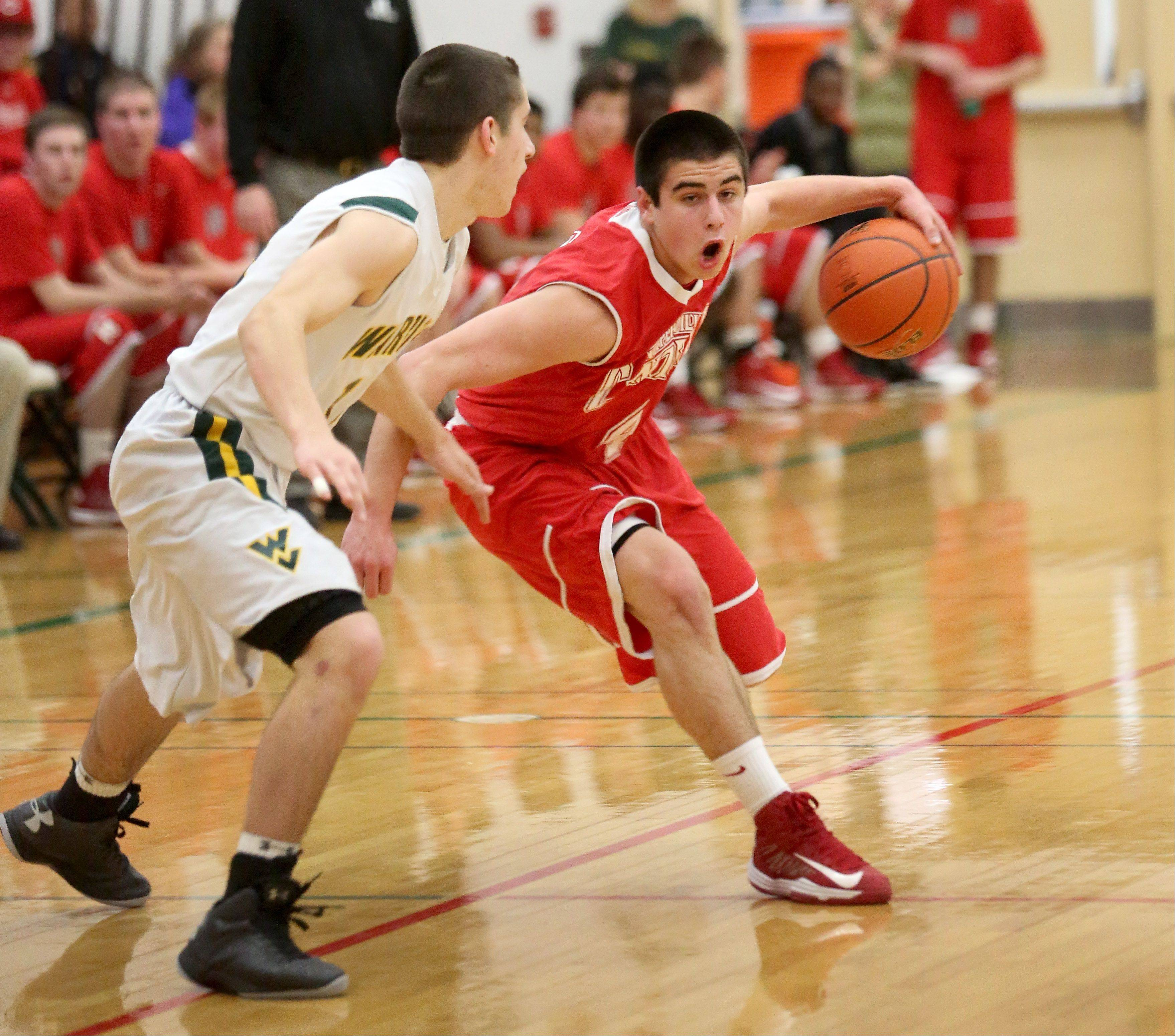 Ryan Antony of Naperville Central, right, moves around Nick Karkazis of Waubonsie Valley in boys basketball action on Tuesday in Aurora.