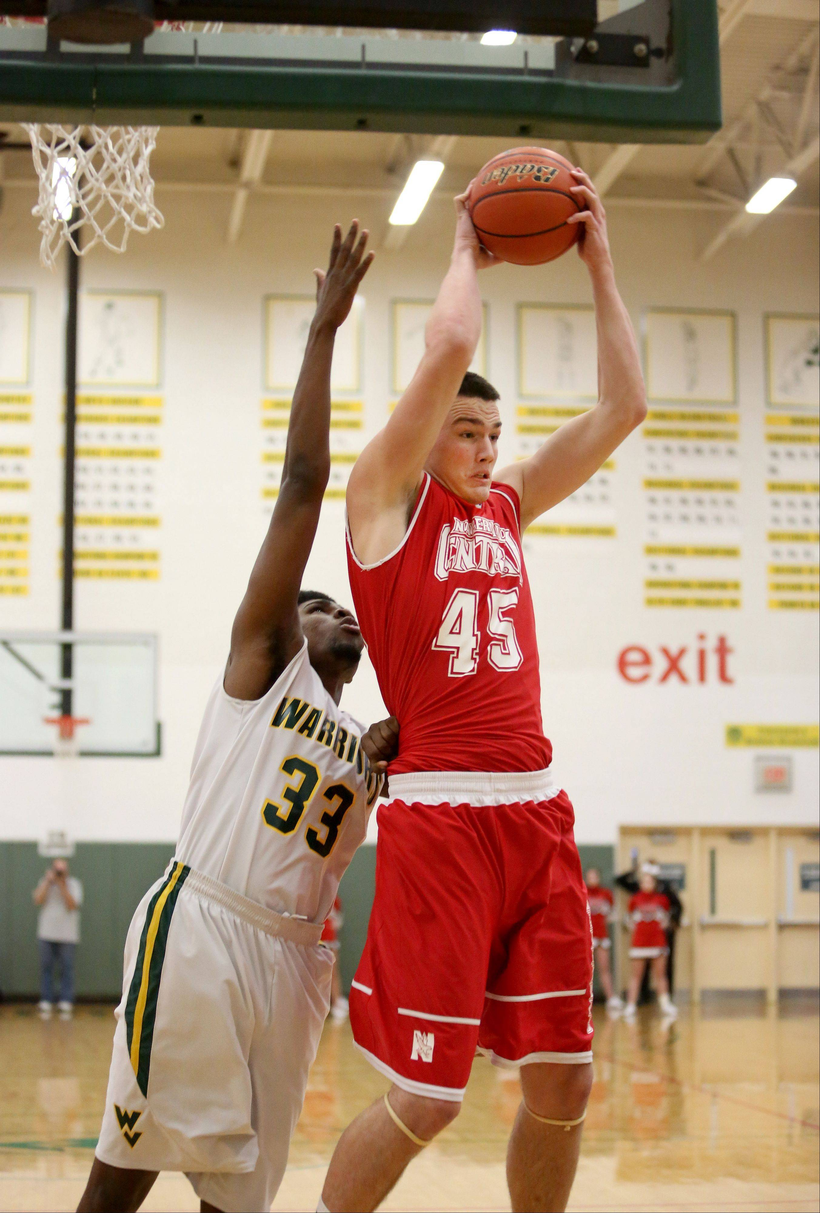 Nick Czarnowski of Naperville Central get the rebound over Javares Stewart of Waubonsie Valley, left, in boys basketball action on Tuesday in Aurora.
