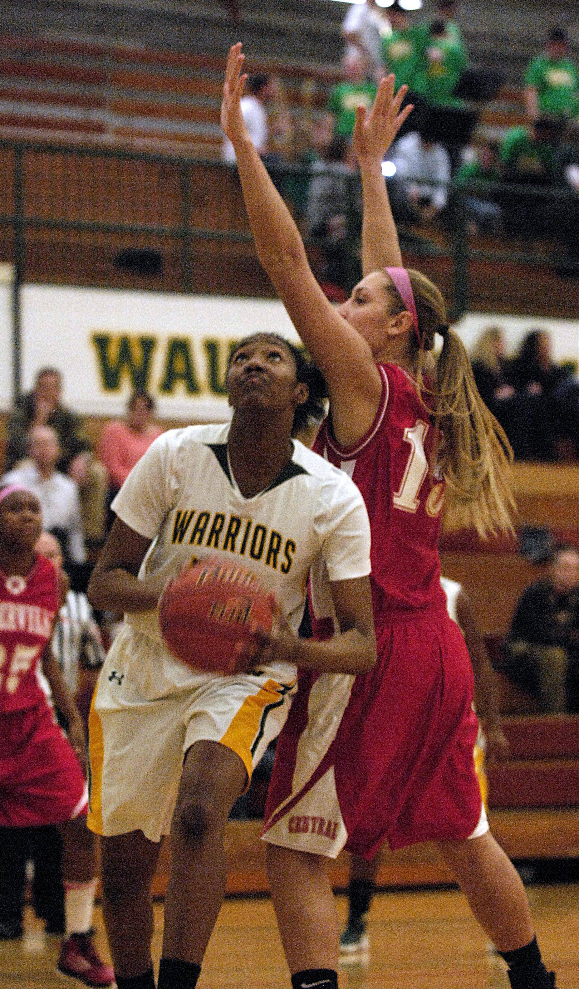 Mark Black/mblack@dailyherald.com Ryaen Johnson of Waubonsie Valley goes up for a shot past Victoria Trowbridge of Naperville Central, Monday night during girls basketball action in Aurora.