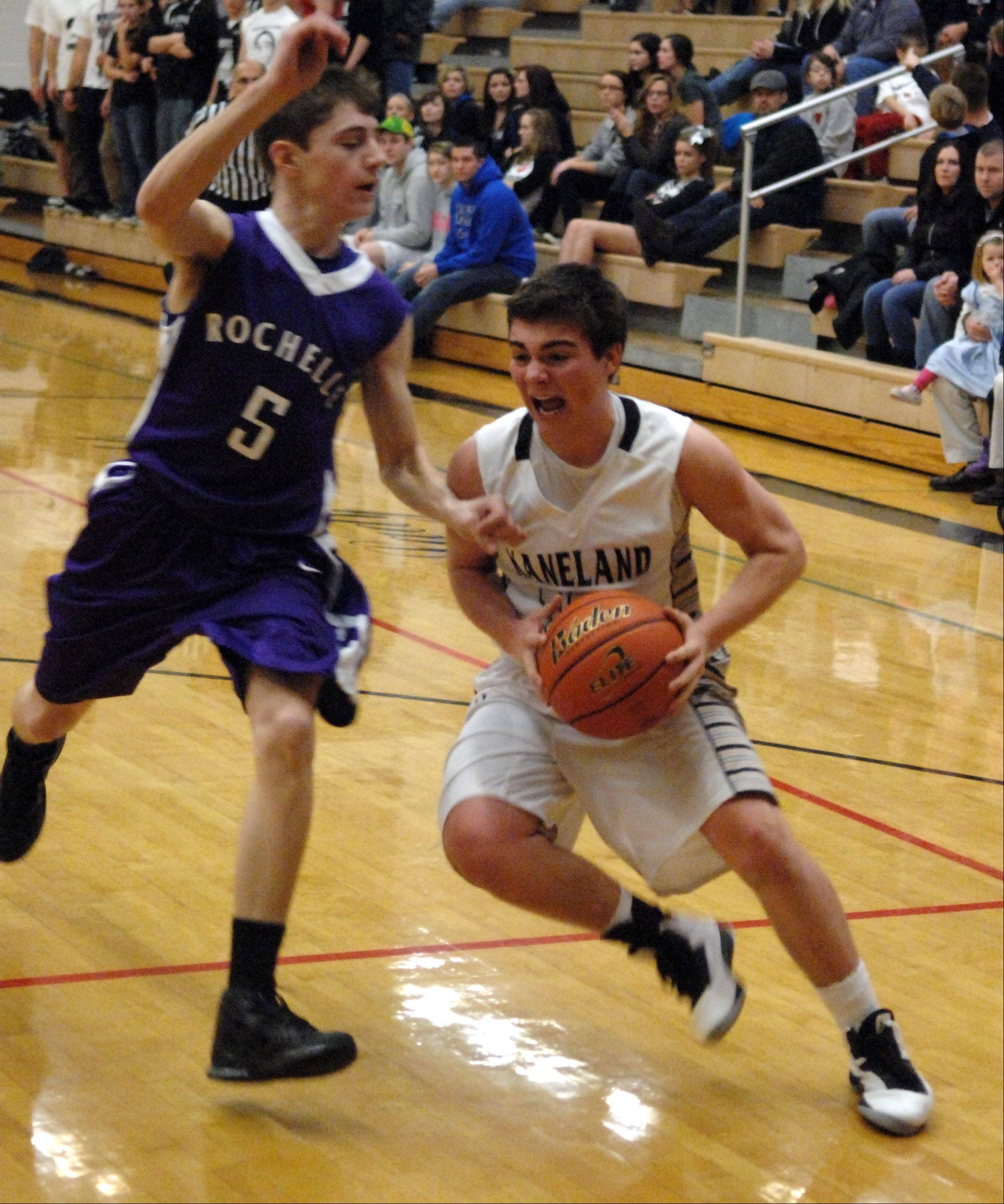 Kaneland's Connor Fedderly tries to drive the baseline as he is defended by Rochelle's Aaron Mehrings.