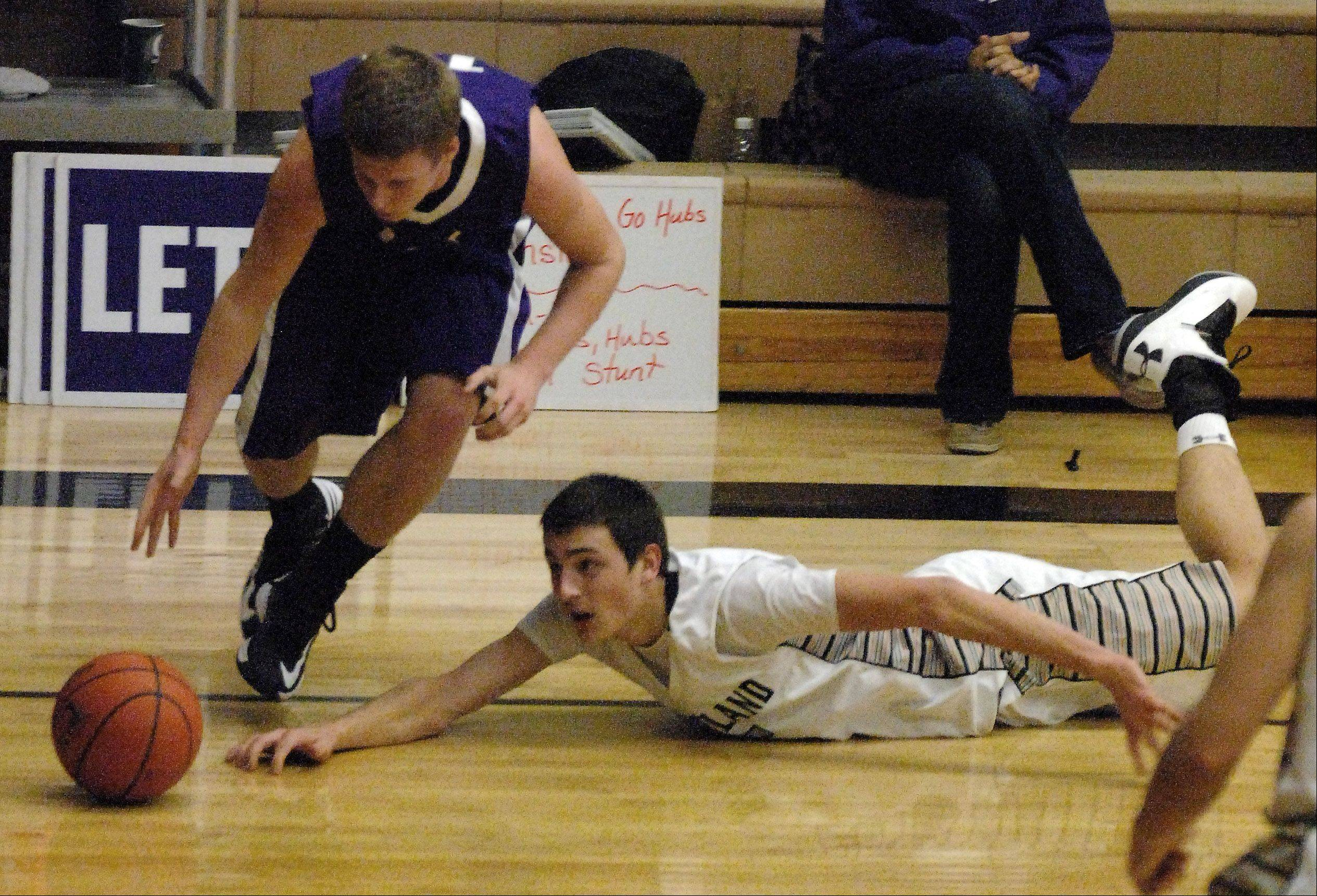Kaneland's John Pruett dives for a loose ball .