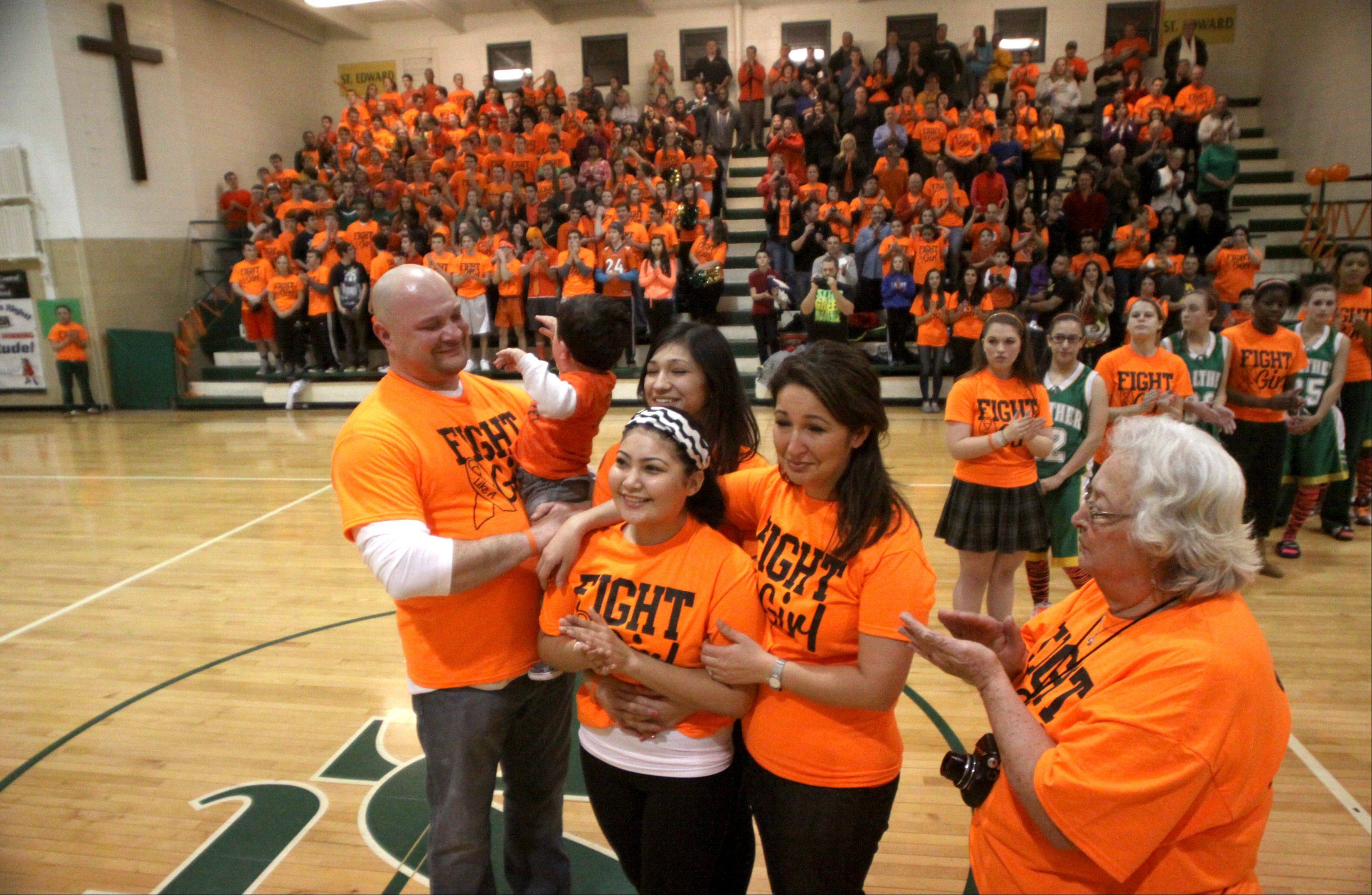 "St. Edward sophomore basketball player Jordan Paz was honored before a varsity contest against Walther Lutheran at Elgin on Thursday night. Paz is undergoing treatment for Leukemia, and school personnel arranged an ""Orange Out Night"" to offer support. Fans donned orange shirts, and team members from both sides formed a receiving line for Paz and her family to enter center court amid cheers and a standing ovation."