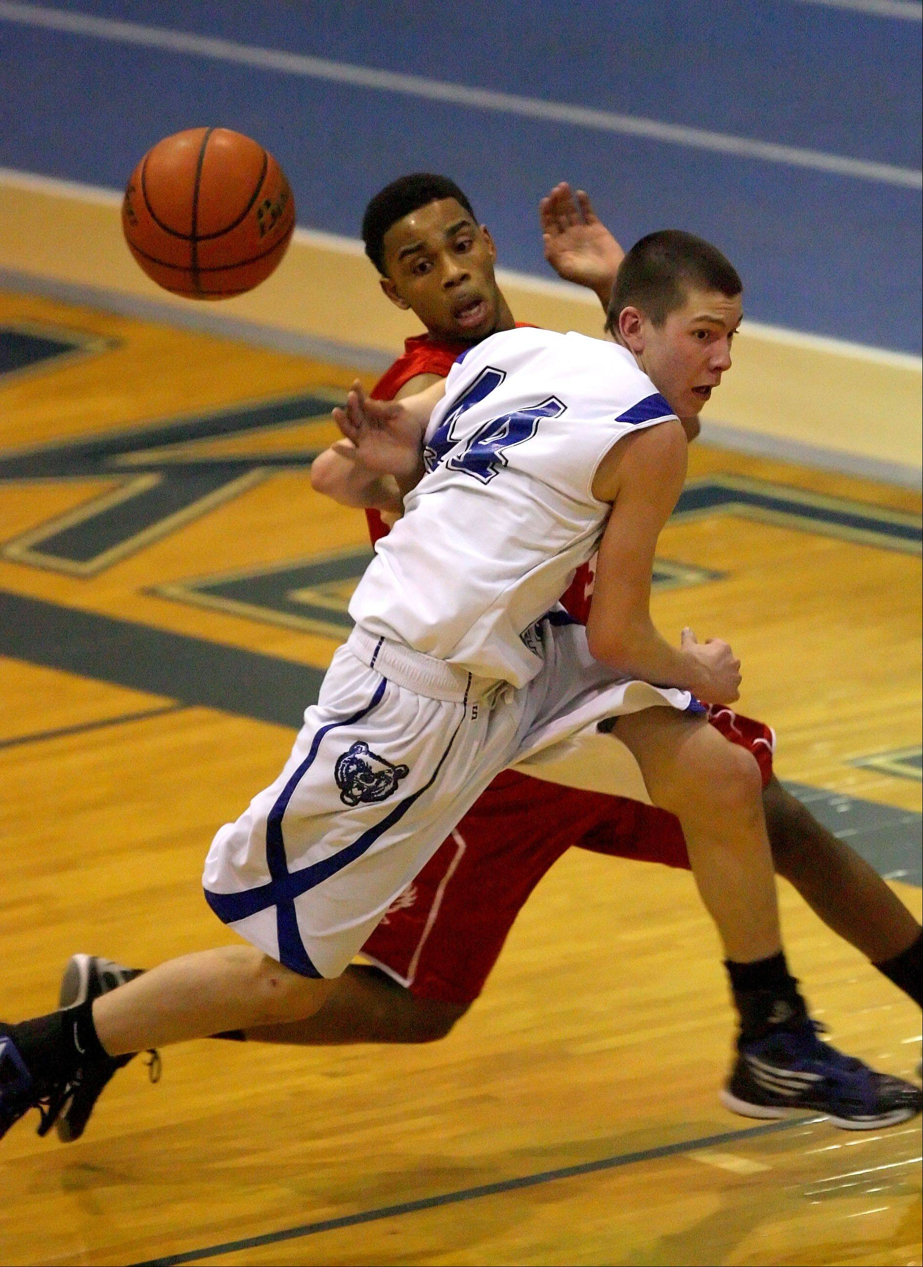 Lake Zurich's Ryan Roach battles for a loose ball against North Chicago's Marzhone Bryant last season. Roach is among the scoring leaders for the Bears this year.