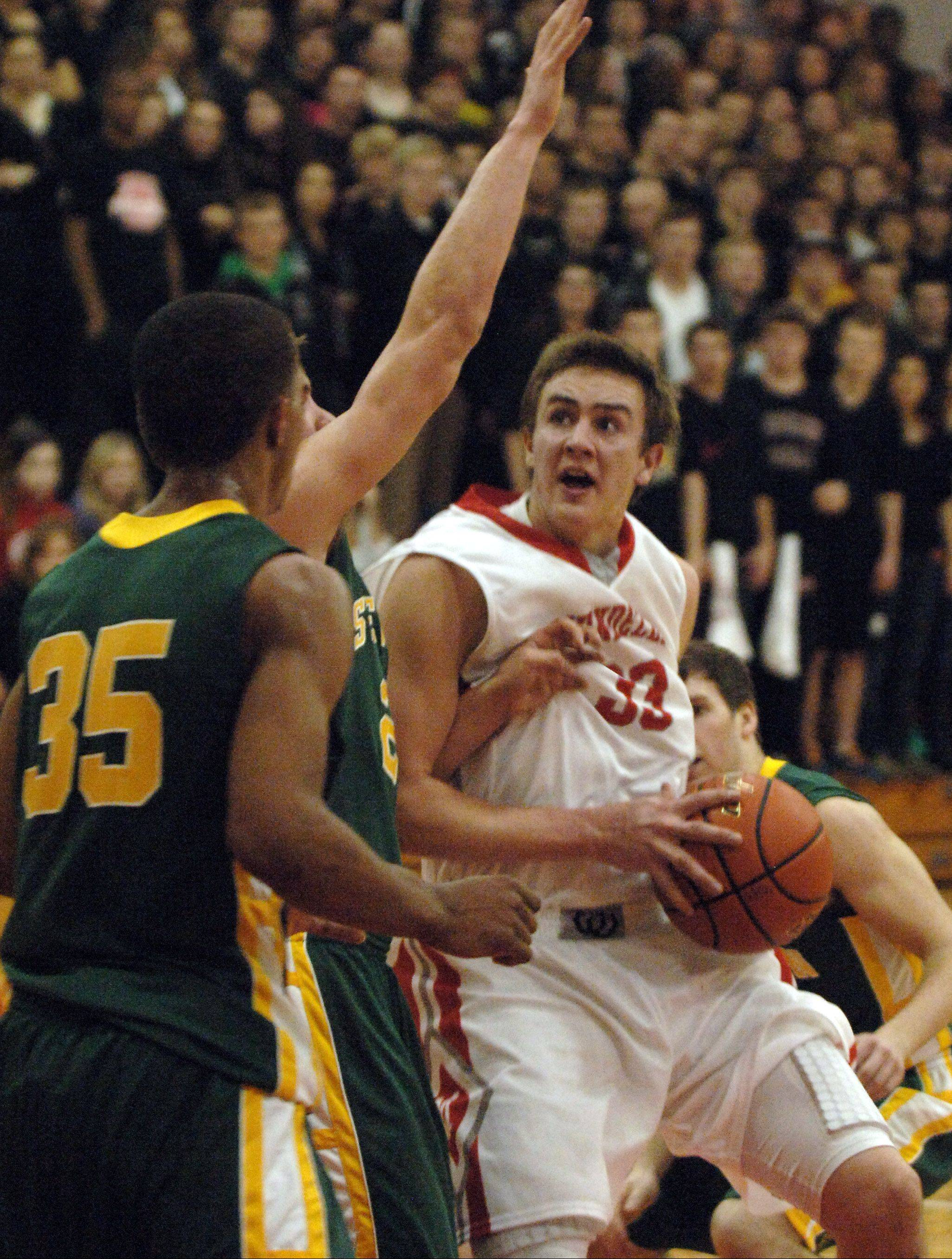 Mundelein's Sean O'Brien, right, heads to the basket under pressure from the Stevenson defense during Friday's game in Mundelein.